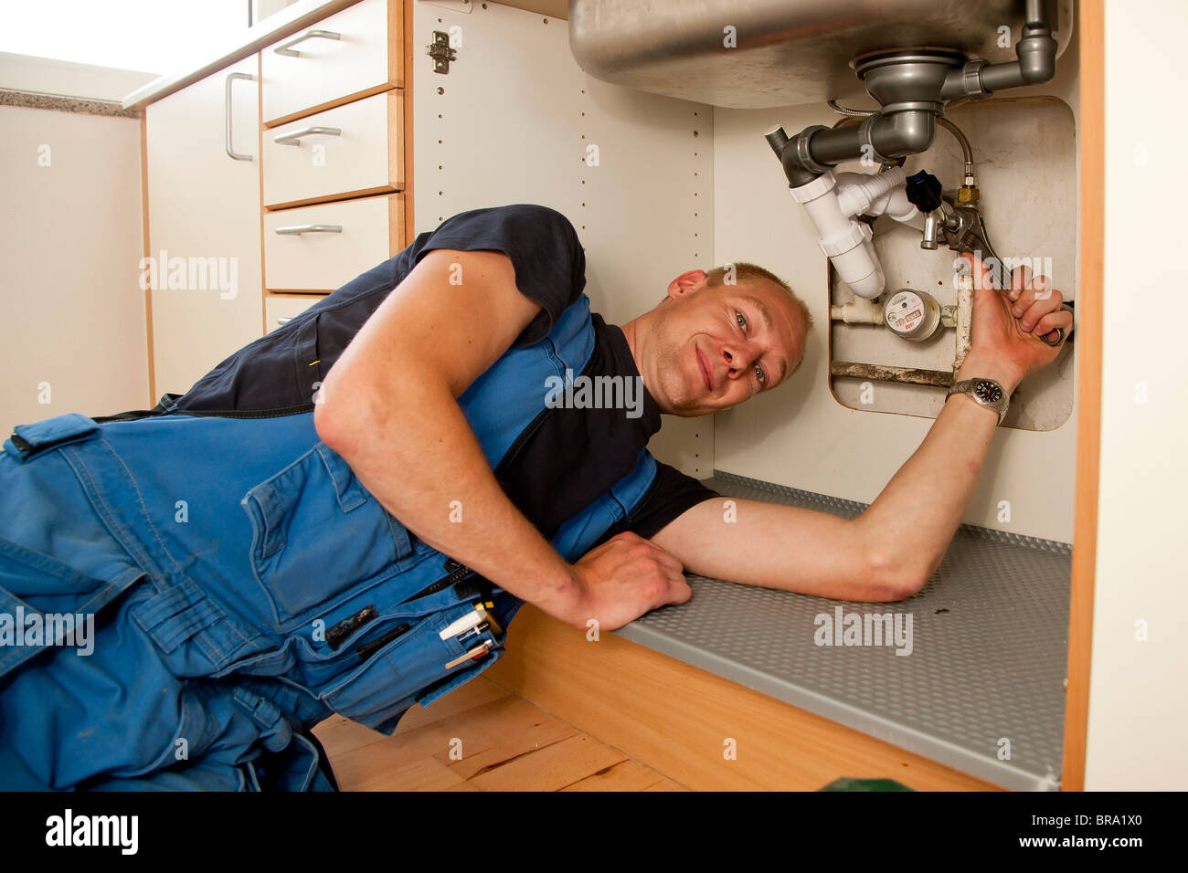 Heating and sanitary technician repairing the leaky pipes under the kitchen sink - Stock Image