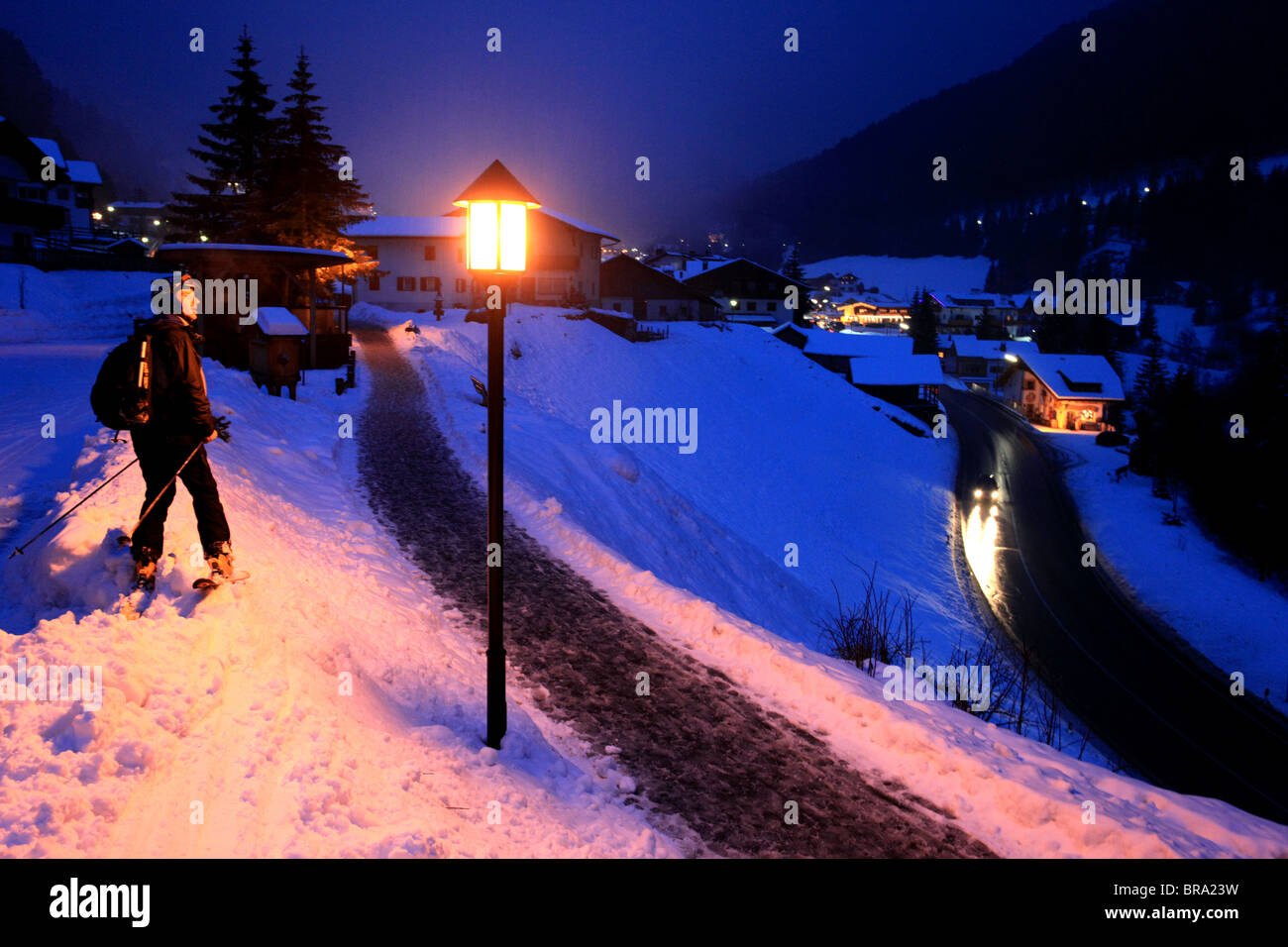A skier standing below a city light at night in Selva Gardena, Val Gardena, Dolomites, Italy - Stock Image