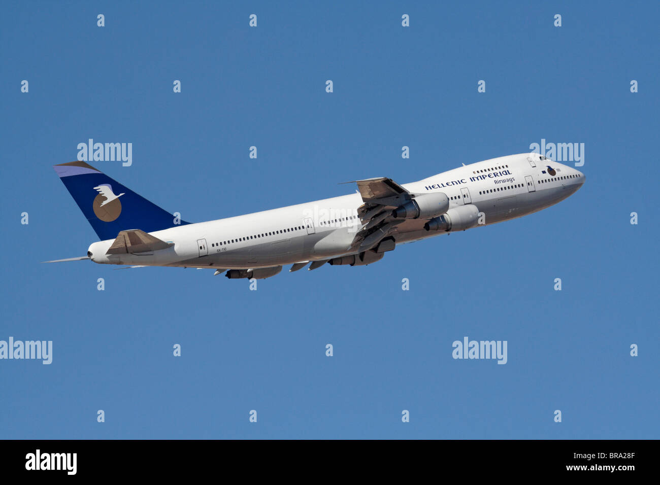 Air travel. Hellenic Imperial Airways Boeing 747-200 flying on departure against a blue sky - Stock Image