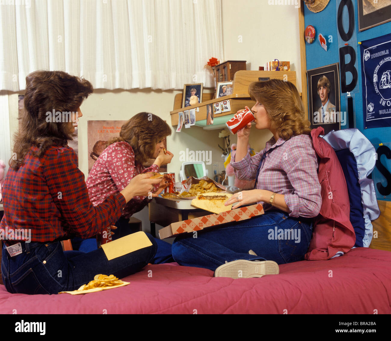 1980s THREE TEENAGE GIRLS EATING PIZZA AND FRENCH FRIES AND DRINKING CANNED SODA IN DORM ROOM Stock Photo