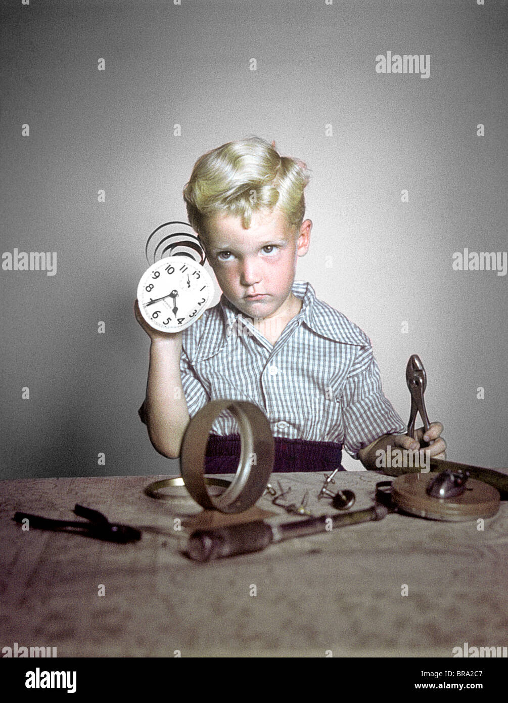 1940s 1950s FUNNY BOY CONFUSED TAKING APART CLOCK TOOLS - Stock Image