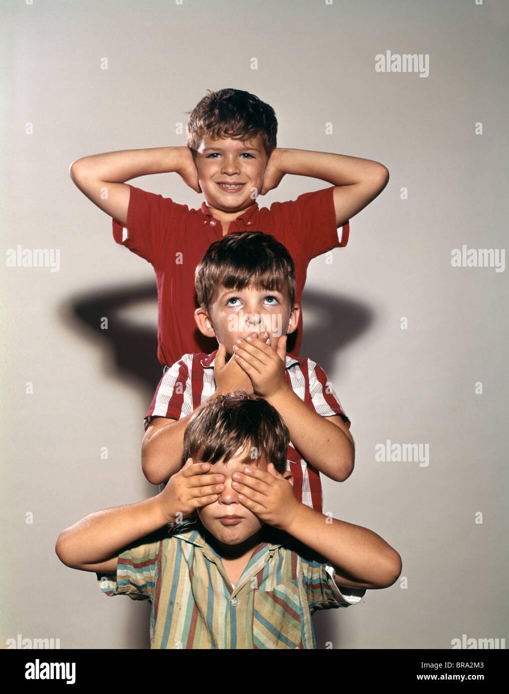 1960s BOYS POSING AS THREE WISE MONKEYS SEE NO EVIL HEAR NO EVIL SPEAK NO EVIL SYMBOLIC STORY - Stock Image