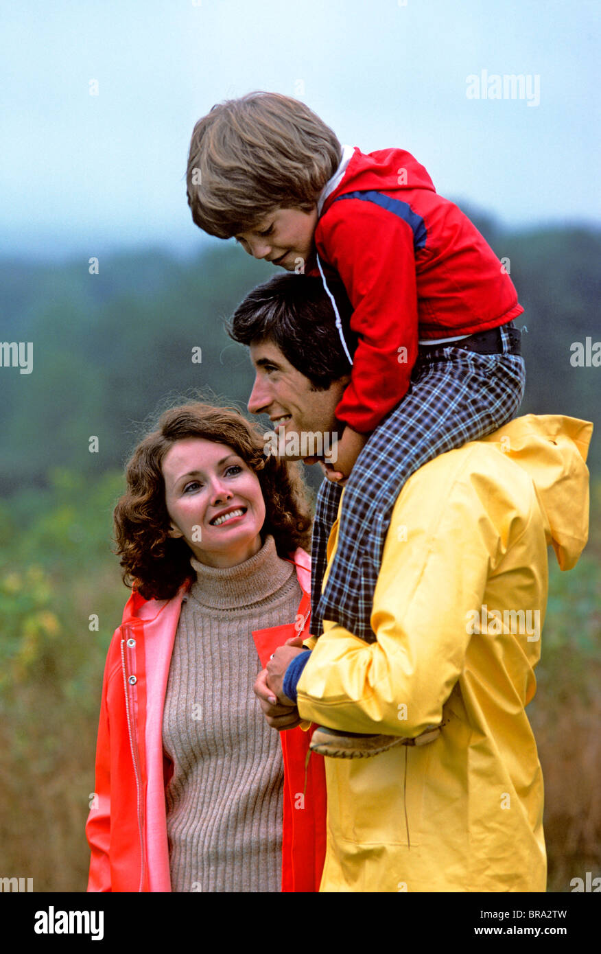 1970 1970s RETRO PARENTS MOTHER FATHER HOLDING SON ON SHOULDERS SMILING FAMILY OUTDOORS - Stock Image