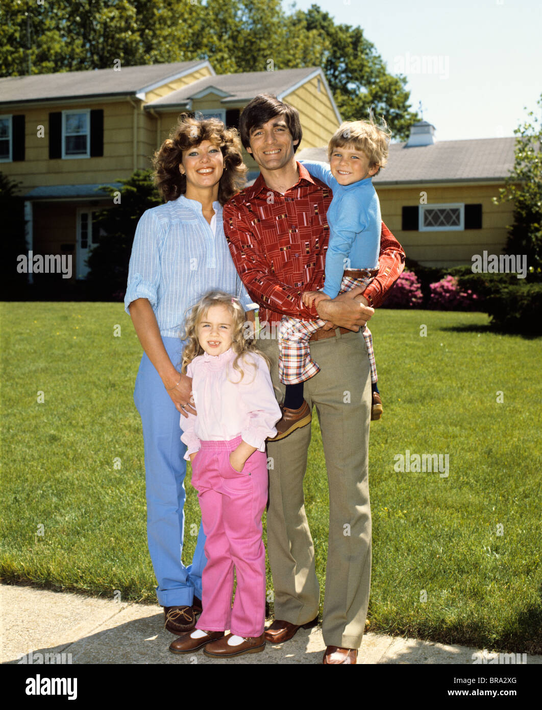 1980s FAMILY IN FRONT OF HOME MOTHER FATHER BOY GIRL PORTRAIT FRONT LAWN RETRO - Stock Image