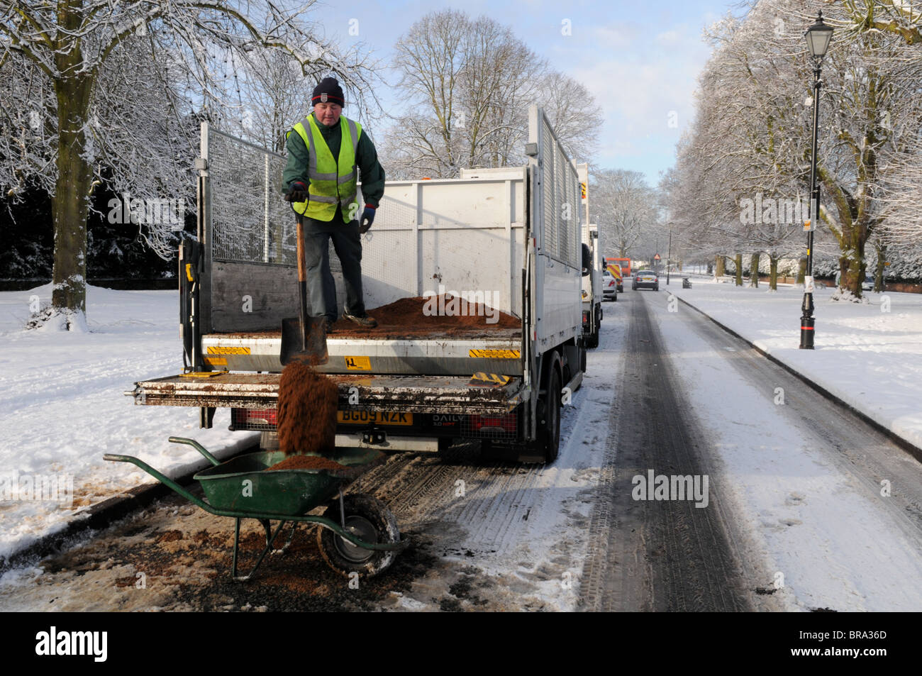 A workman shovels grit from the back of a lorry into a wheelbarrow on a snow-covered road in Tettenhall, Wolverhampton. - Stock Image