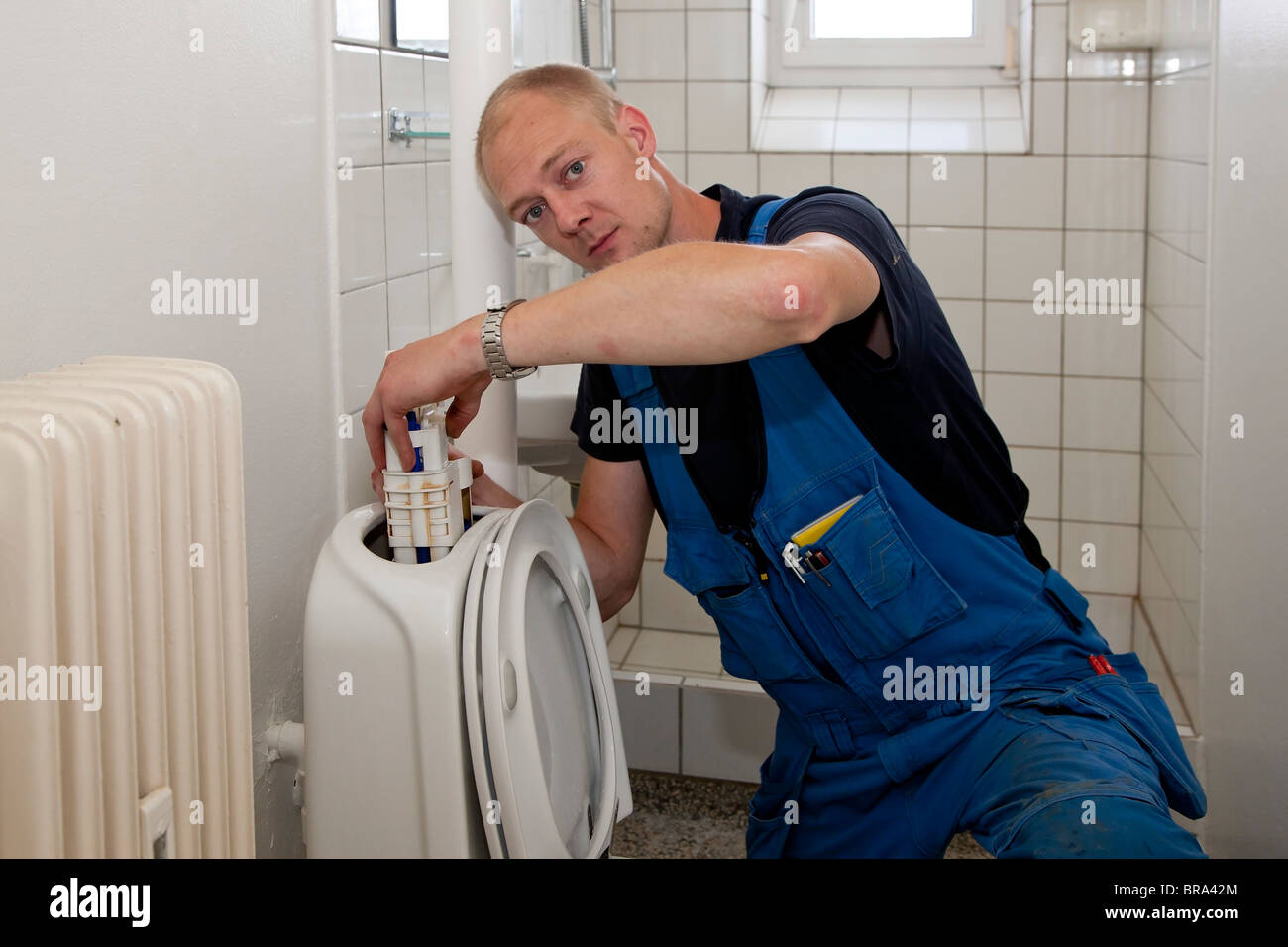 Heating and sanitary technician repairing the toilet cistern - Stock Image