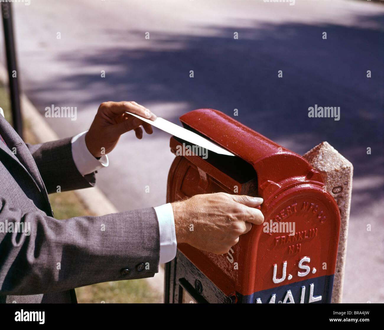 1960s MALE HAND DROPPING LETTER INTO U.S. POSTAL MAILBOX MAN MAILING LETTER - Stock Image
