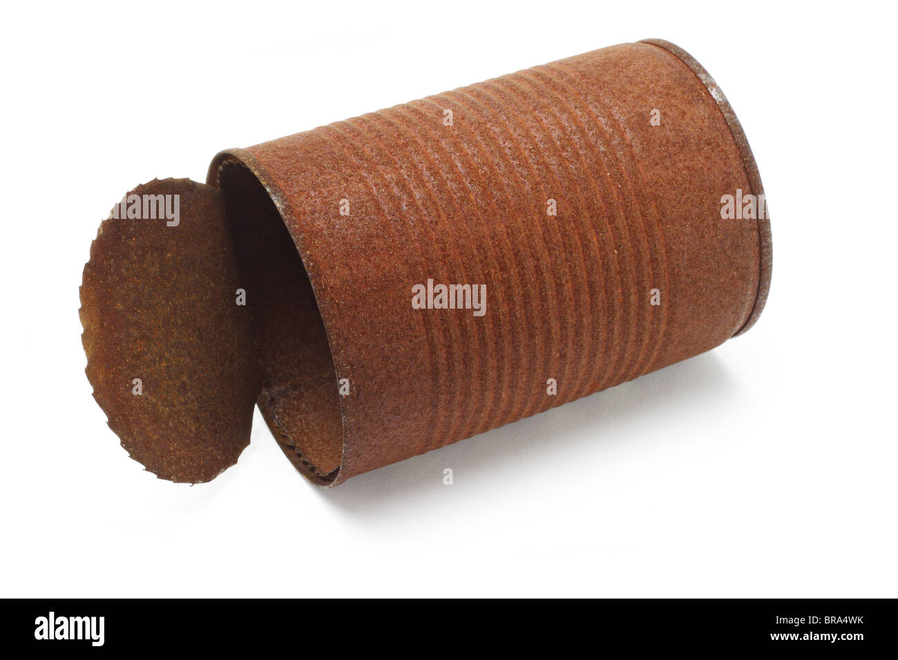 Old rusty tin can lying on white background - Stock Image