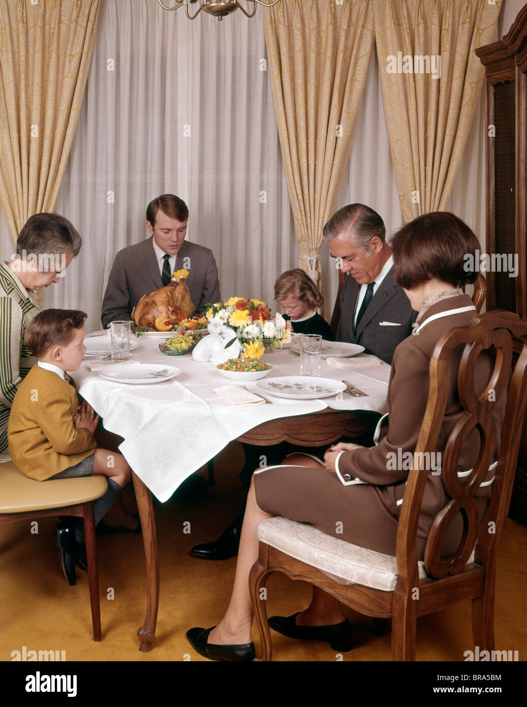 1960s 1970s THREE GENERATION FAMILY SAYING GRACE PRAYER THANKSGIVING DINNER - Stock Image