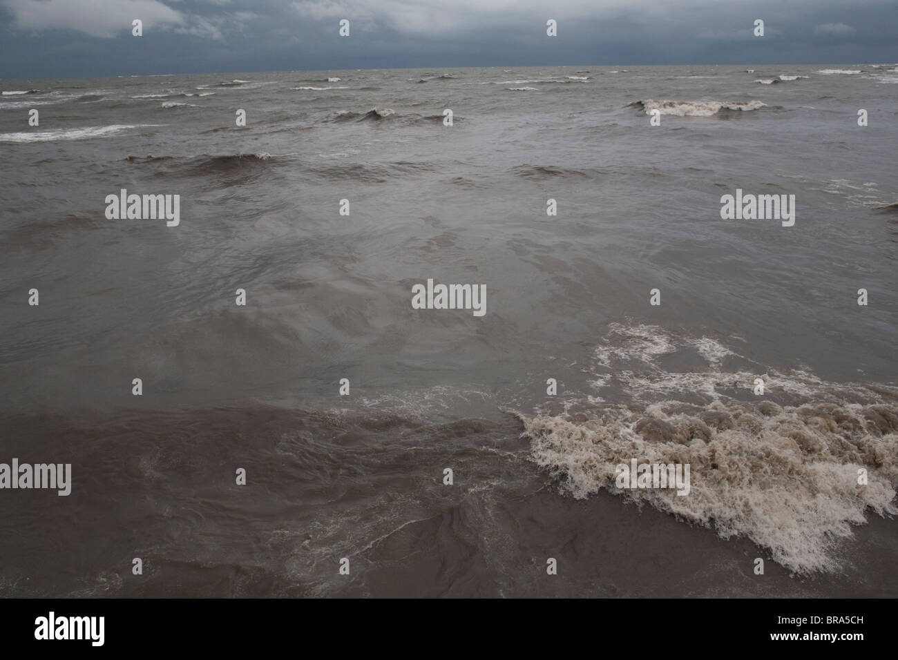 An oil slick from the Deepwater Horizon BP oil spill coats the waves in Grand Isle, Louisiana. - Stock Image