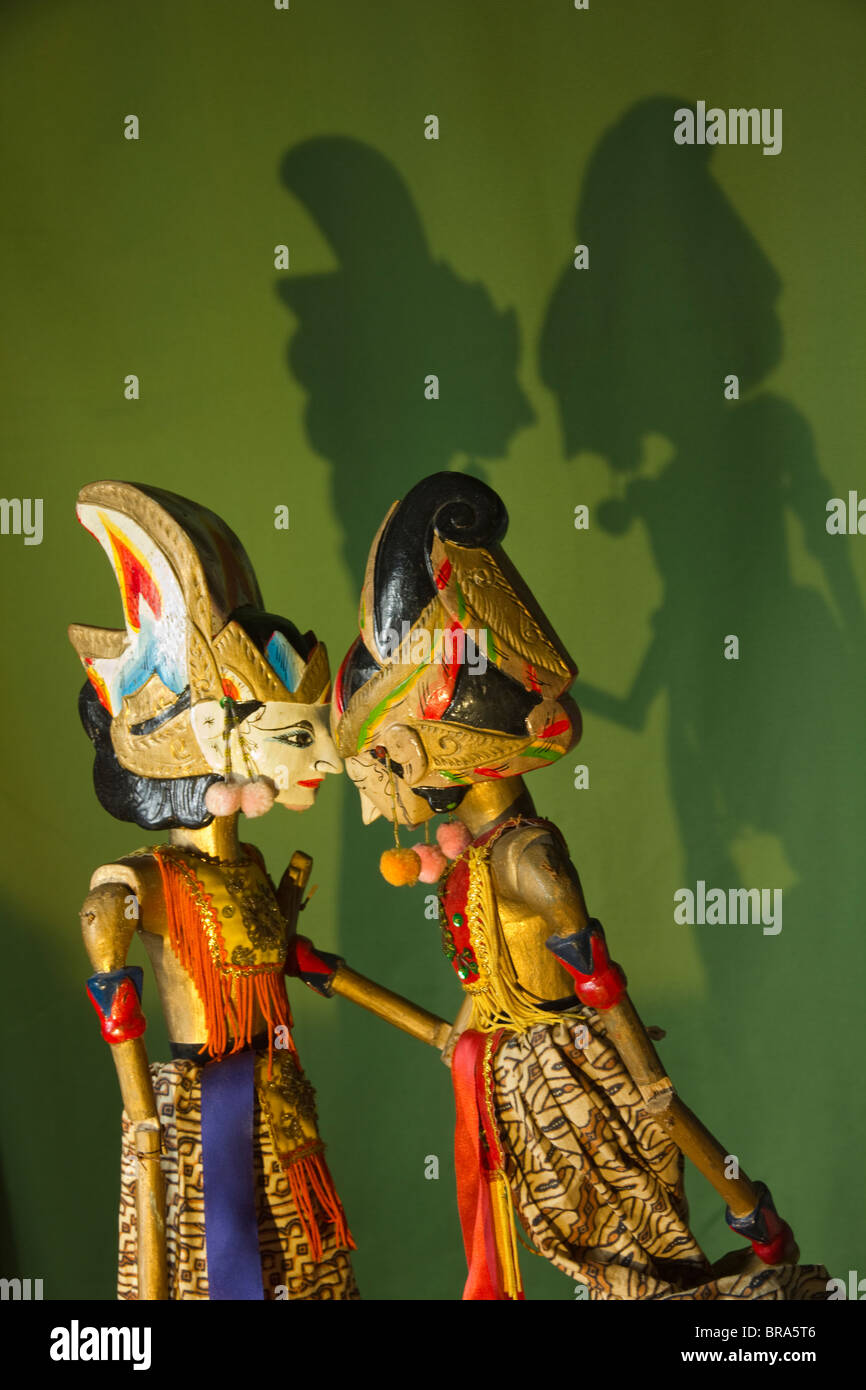 Shadow puppets against a green backdrop with shadows. - Stock Image