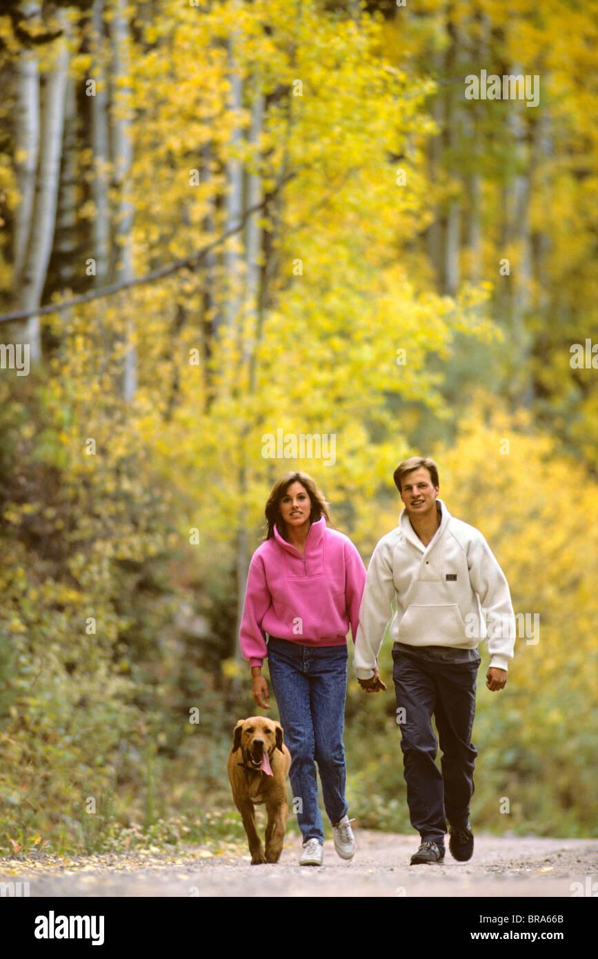 COUPLE WALKING WITH DOG - Stock Image