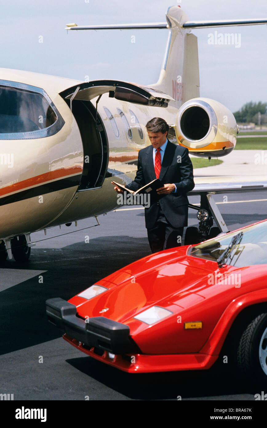 Business Man Standing Between Lamborghini And Lear Jet Stock Photo