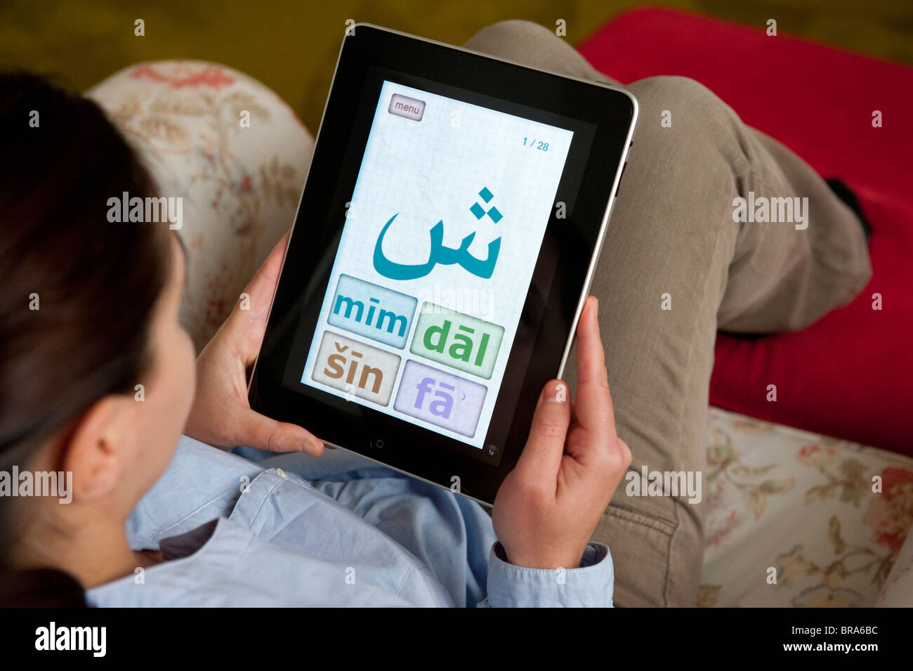 Female student learning Arabic language using education application on iPad tablet computer - Stock Image