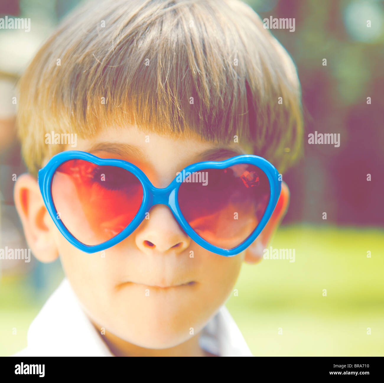 Young boy in heart shaped sunglasses - Stock Image