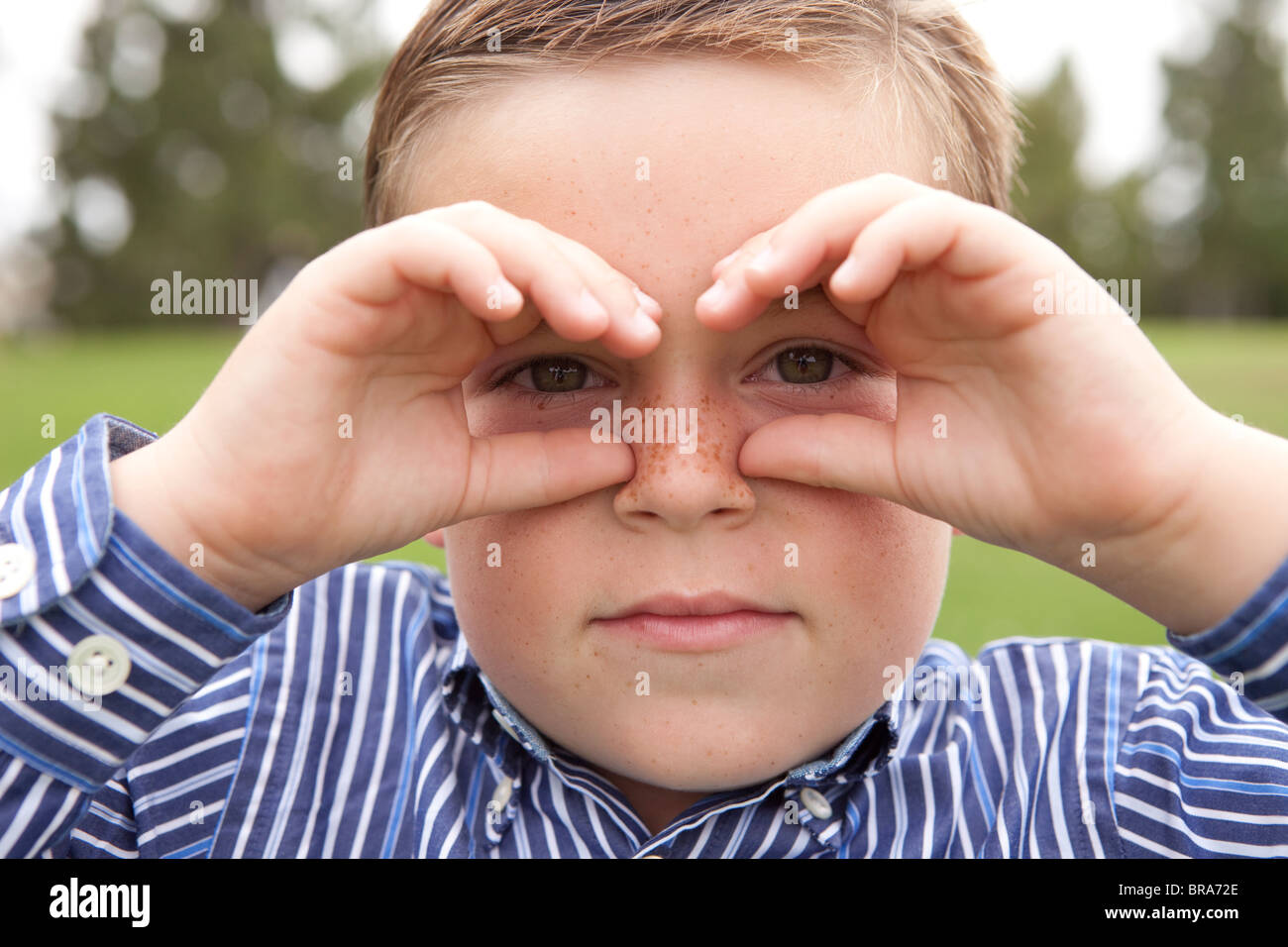 Freckled boy cupping his eyes - Stock Image