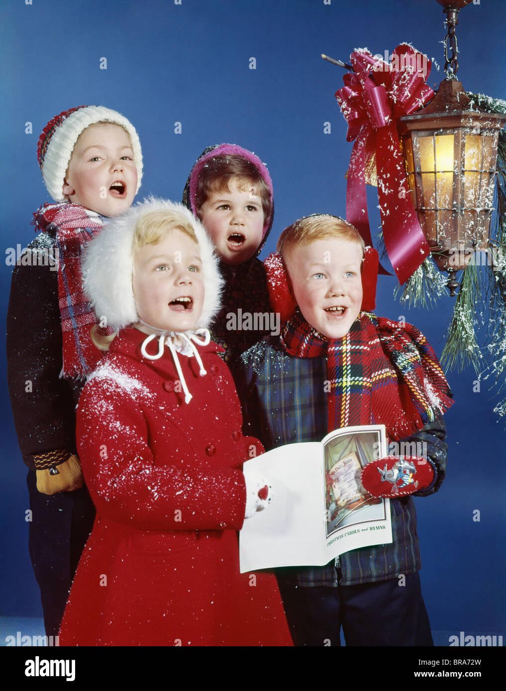 1960 1960s RETRO CHILDREN SINGING CAROLS LAMP CAROLERS CHRISTMAS - Stock Image