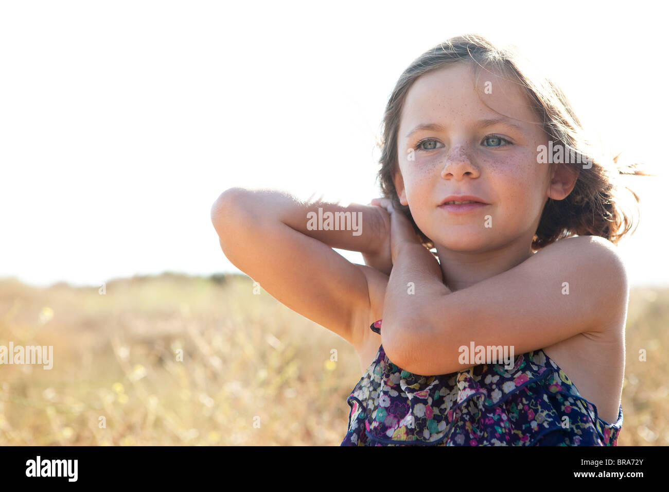 Little girl playing in a field - Stock Image