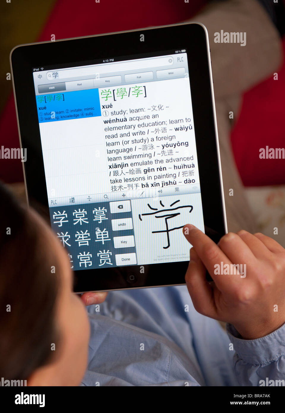 Female student learning mandarin Chinese using education application on iPad tablet computer - Stock Image