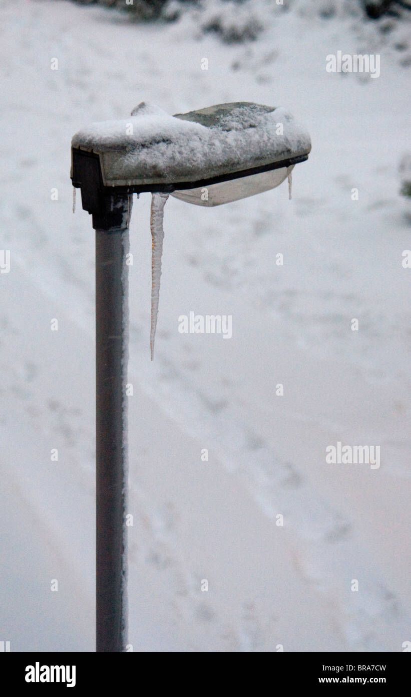 A modern streetlight, with an icicle hanging from it in freezing weather. - Stock Image