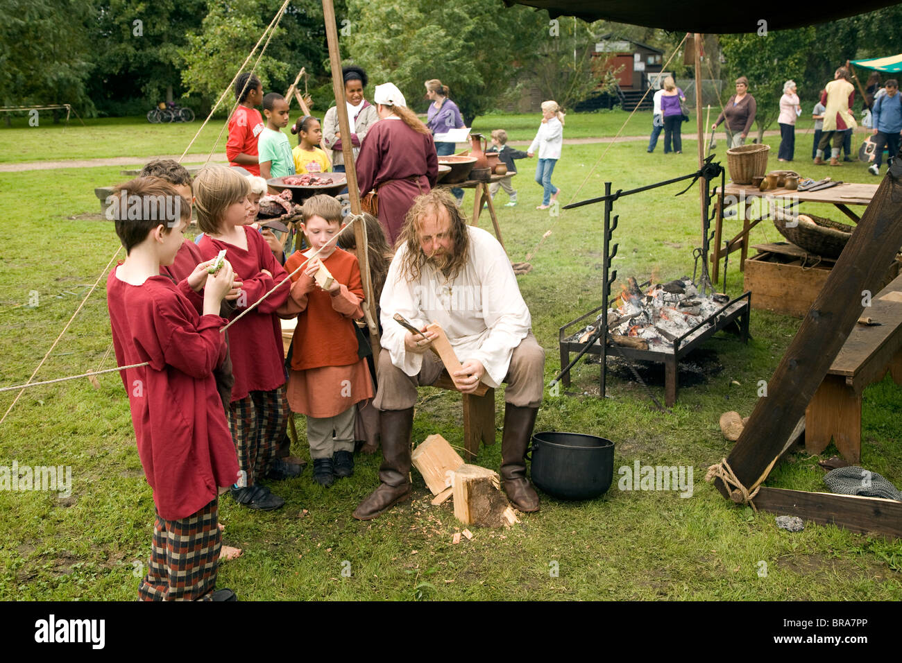 Man teaching children woodcraft, Historical re-enactment Saxon, Viking, Norman history, Woodbridge, Suffolk - Stock Image