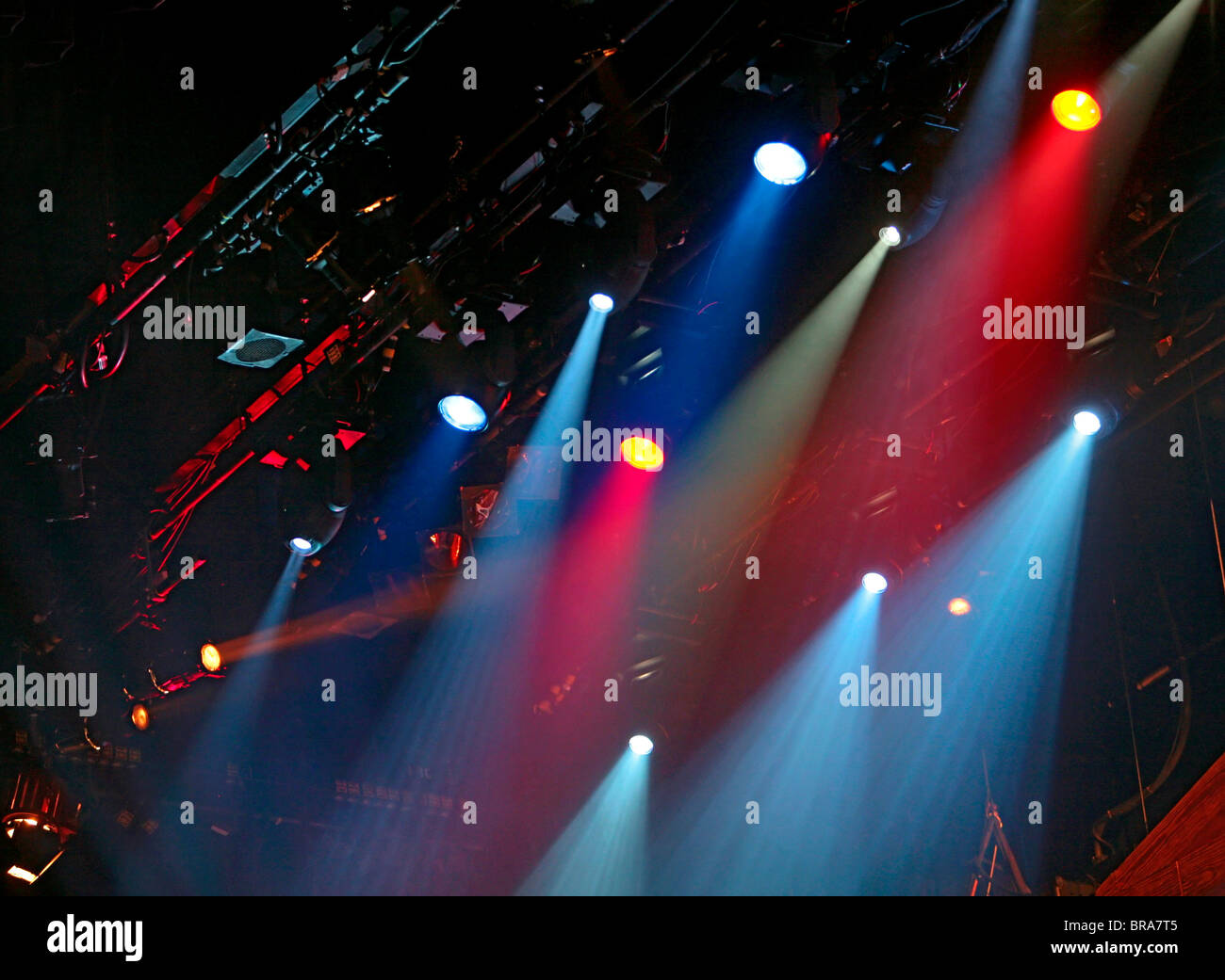 blue and red stage lighting against a dark black background - Stock Image