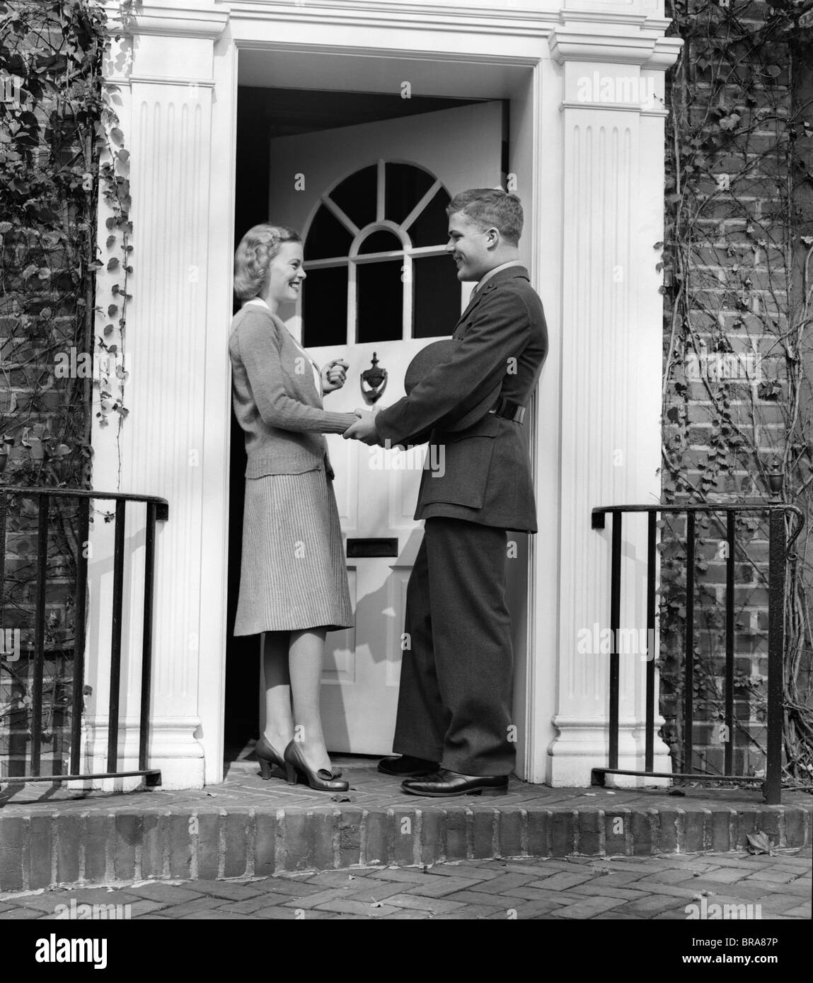 1940s WOMAN GREETING MAN IN SOLDIERS UNIFORM AT FRONT DOOR & 1940s WOMAN GREETING MAN IN SOLDIERS UNIFORM AT FRONT DOOR Stock ...