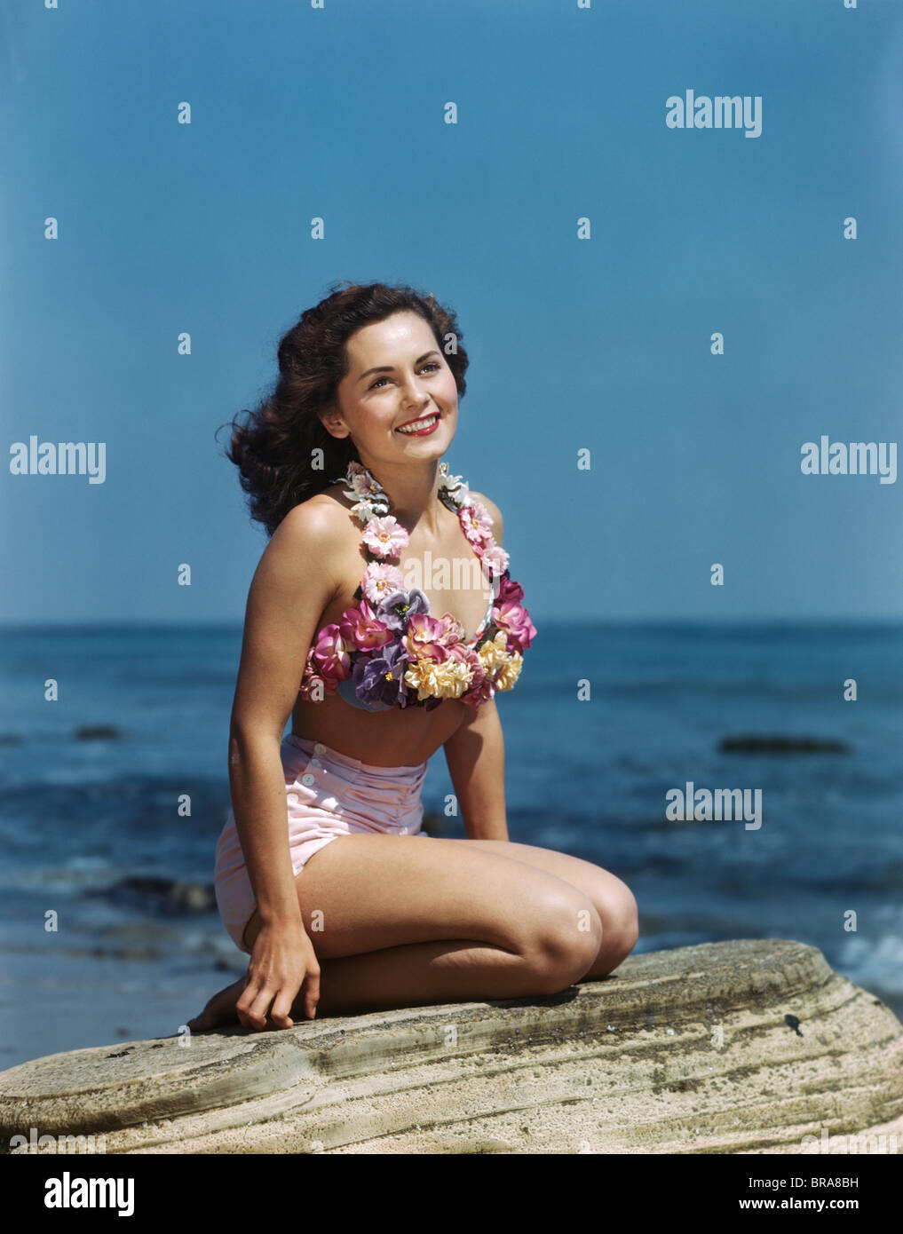 1940s 1950s SMILING BRUNETTE WOMAN SITTING ON ROCK WEARING TWO PIECE BATHING SUIT APPLIQUÉD WITH PASTEL FLOWERS - Stock Image