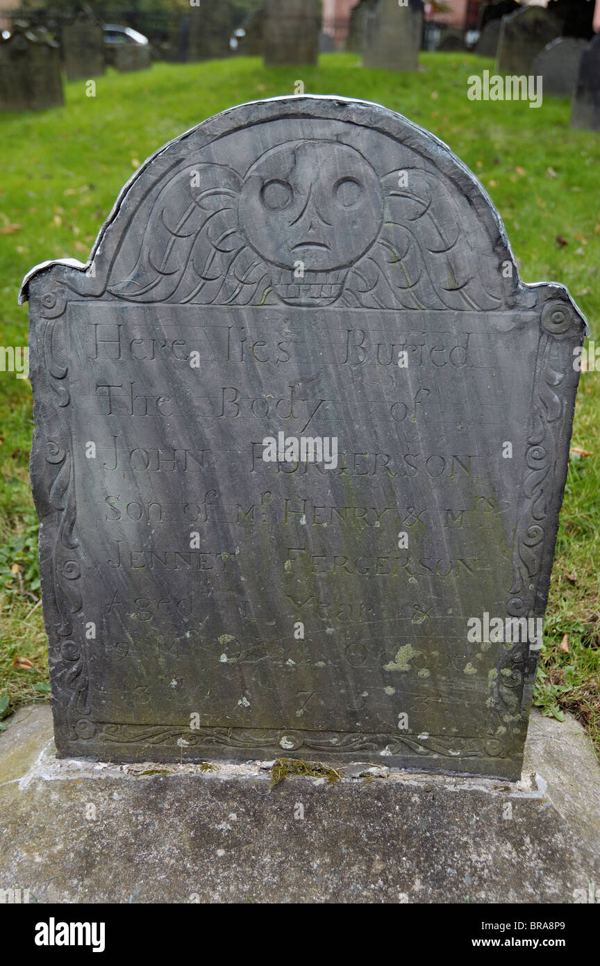 An old gravestone showing the deaths head - Stock Image