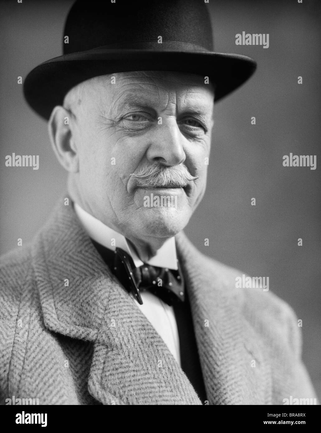 1930s PORTRAIT OF OLDER MAN WITH A MUSTACHE WEARING A BOWLER HAT AND BOW TIE - Stock Image