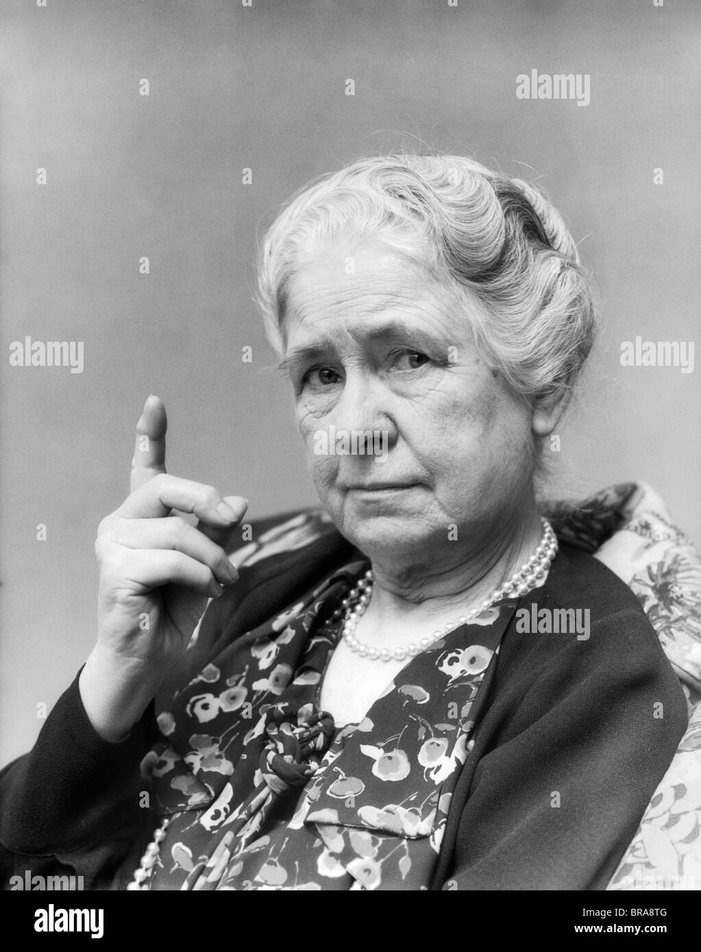 1930s PORTRAIT OF ELDERLY WOMAN WITH FINGER RAISED AT VIEWER - Stock Image