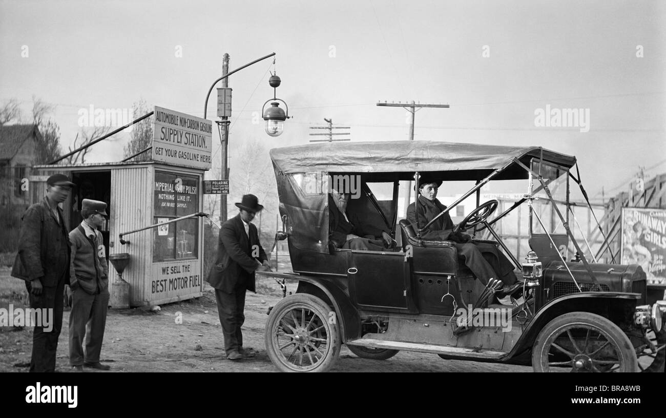 1910s KANSAS CITY MISSOURI MAN FILLING TANK OF OLD CAR AT GASOLINE STATION NEXT TO THE OLD SANTA FE TRAIL - Stock Image
