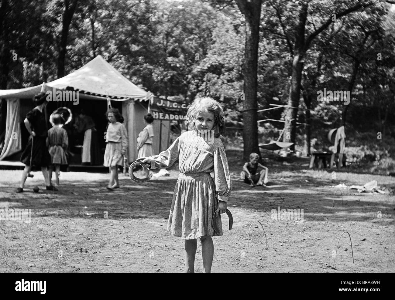 1910s LITTLE GIRL PITCHING HORSESHOES IN A GIRLS SUMMER CAMP KANSAS CITY MISSOURI - Stock Image