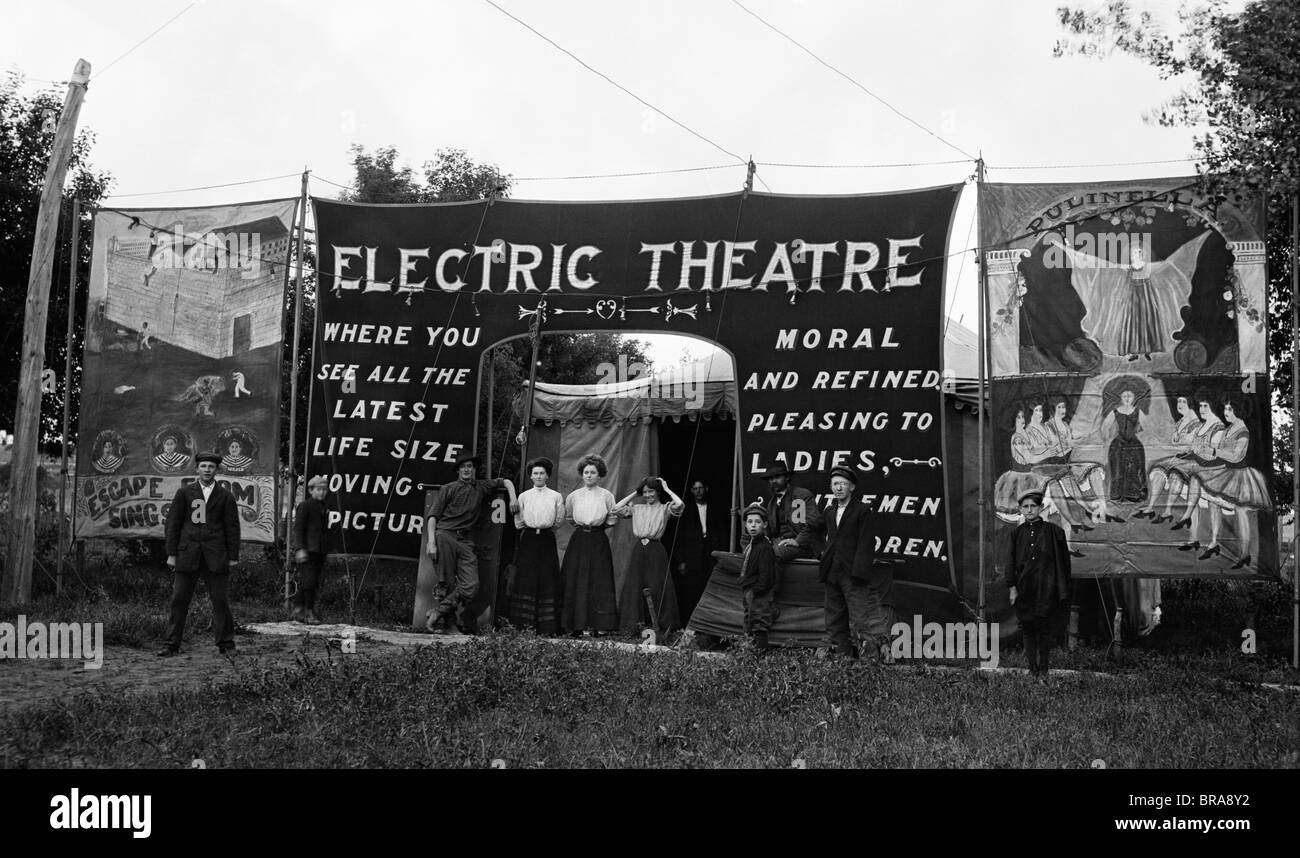 1900s 1910s GROUP PEOPLE STANDING AT ENTRANCE OUTDOOR TRAVELING MOVING PICTURE THEATER - Stock Image