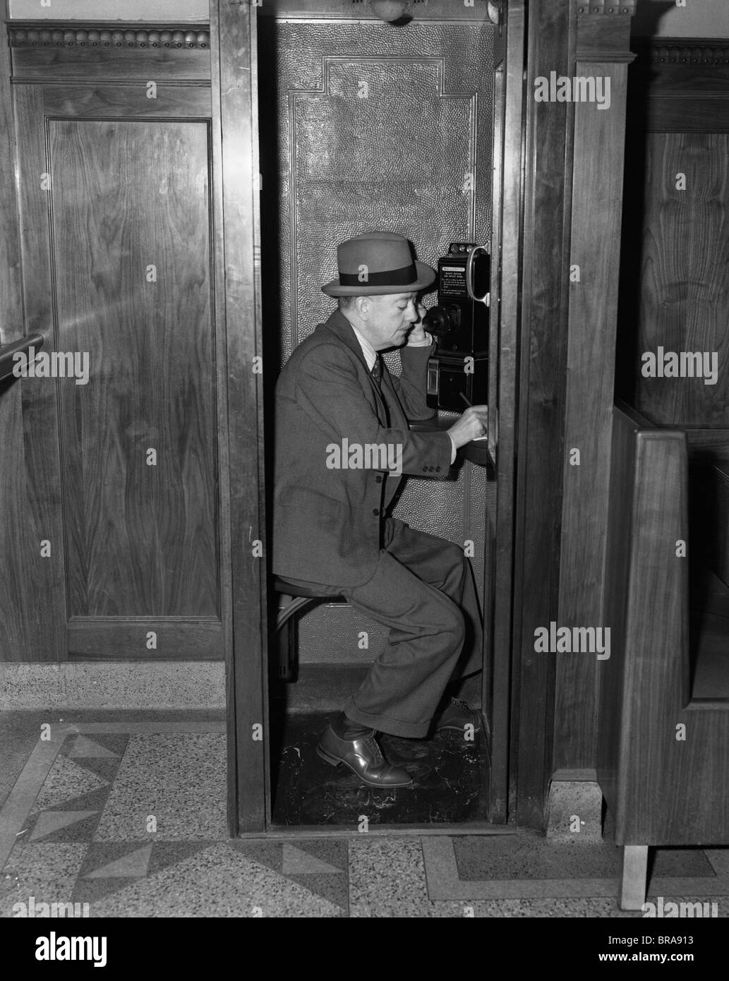 1940s MAN SITTING IN WOODEN TELEPHONE BOOTH SPEAKING INTO RECEIVER - Stock Image