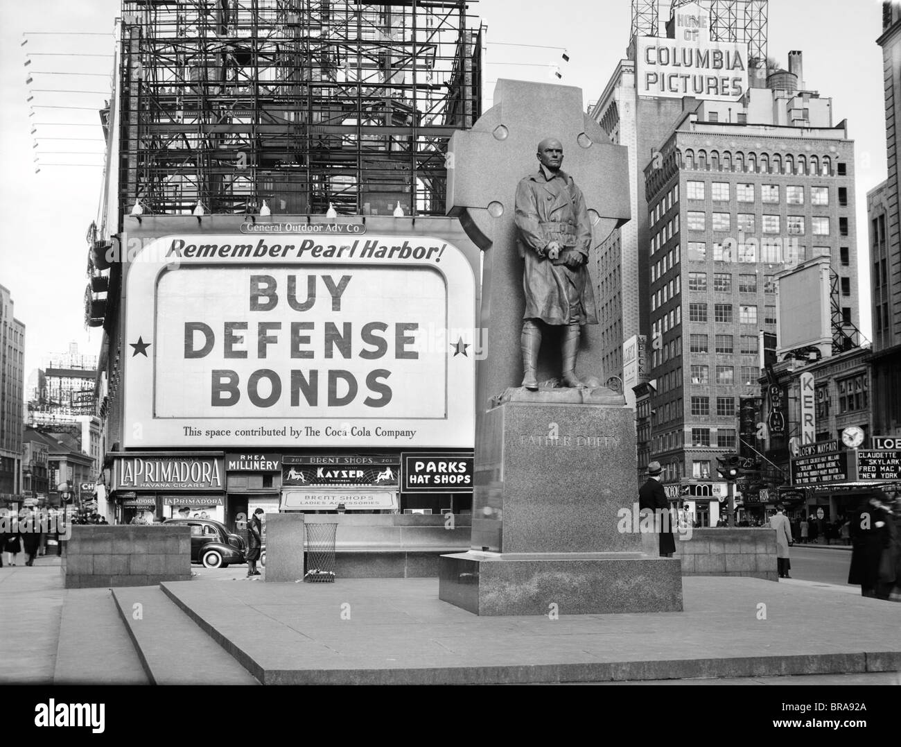 1940s BUY DEFENSE BONDS BILLBOARD AT STATUE OF FATHER DUFFY OF THE FIGHTING 69th OF WORLD WAR I AT TIMES SQUARE - Stock Image