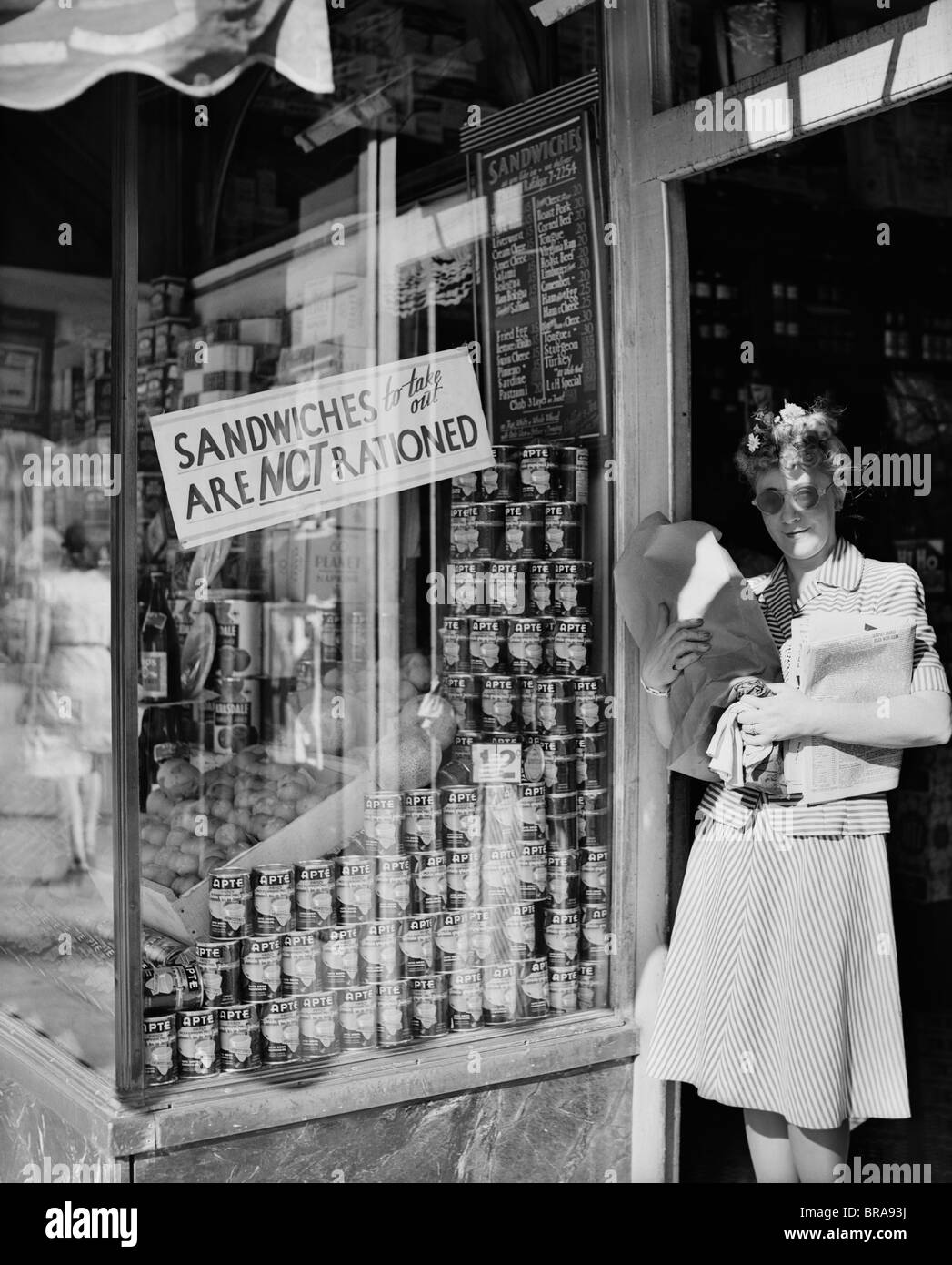 1940s WOMAN CARRYING PACKAGES IN DOOR OF NEW YORK CITY DELICATESSEN DISPLAYING A SIGN SANDWICHES TO TAKE OUT ARE NOT RATIONED & 1940s WOMAN CARRYING PACKAGES IN DOOR OF NEW YORK CITY DELICATESSEN ...