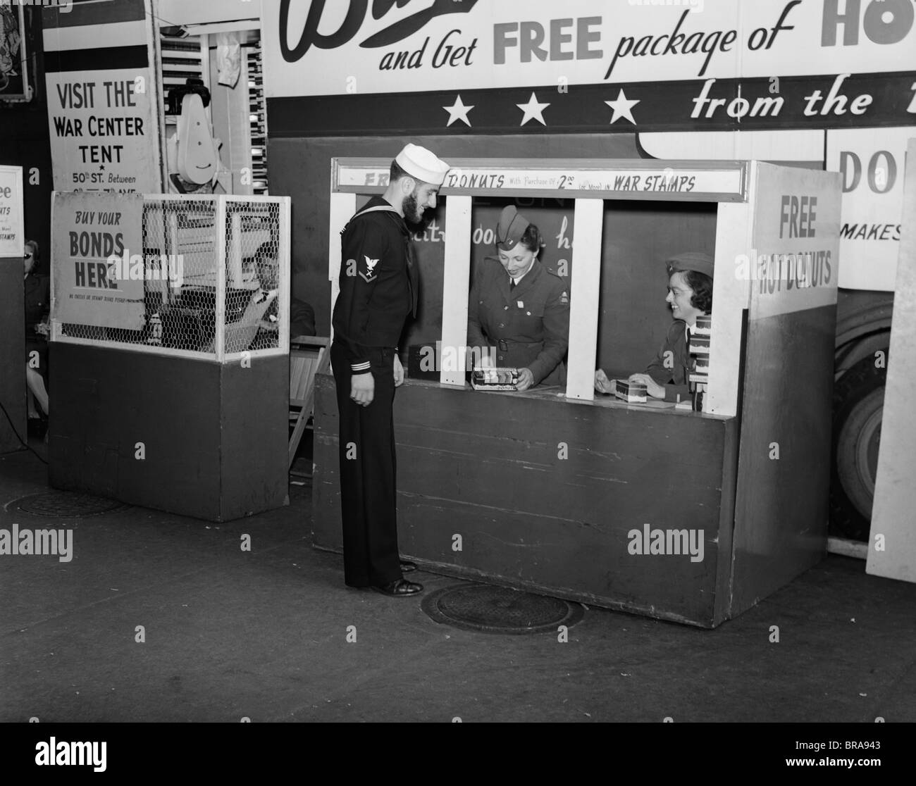 1940s 1943 SAILOR BUYING WAR STAMPS AT DONUT MOBILE AT BOWLING GREEN NEW YORK CITY - Stock Image