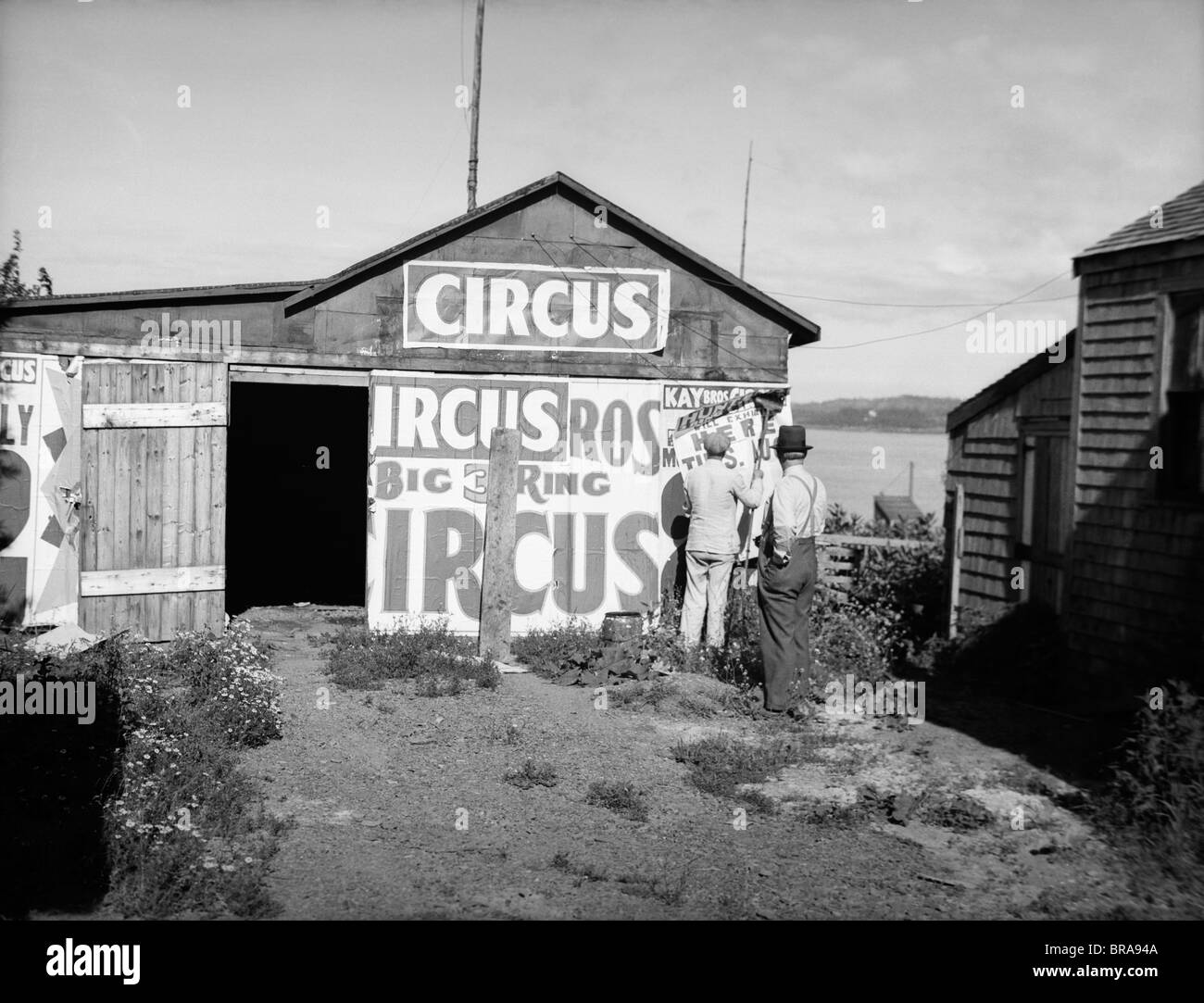 1920s BILL POSTERS STICKING SIGNS ON THE SIDE OF A BARN ADVERTISING A TRAVELING CIRCUS - Stock Image