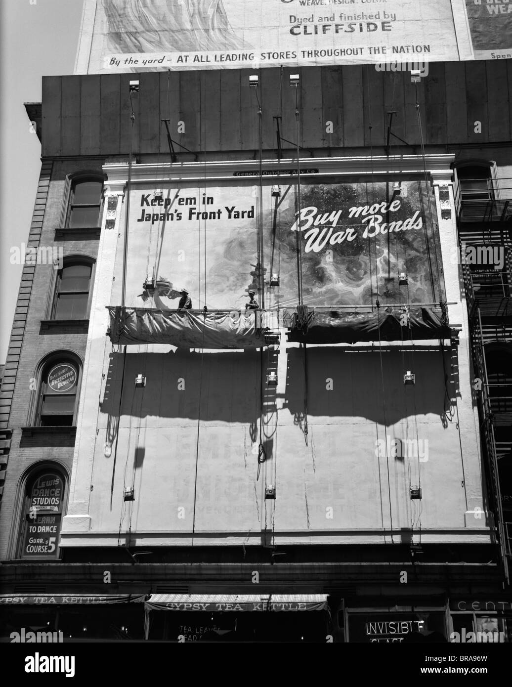 1940s 1945 NEW YORK CITY SIGN PAINTERS CORNER 42nd STREET FIFTH AVENUE PAINTING NEW WAR BONDS SIGN FROM SCAFFOLD - Stock Image
