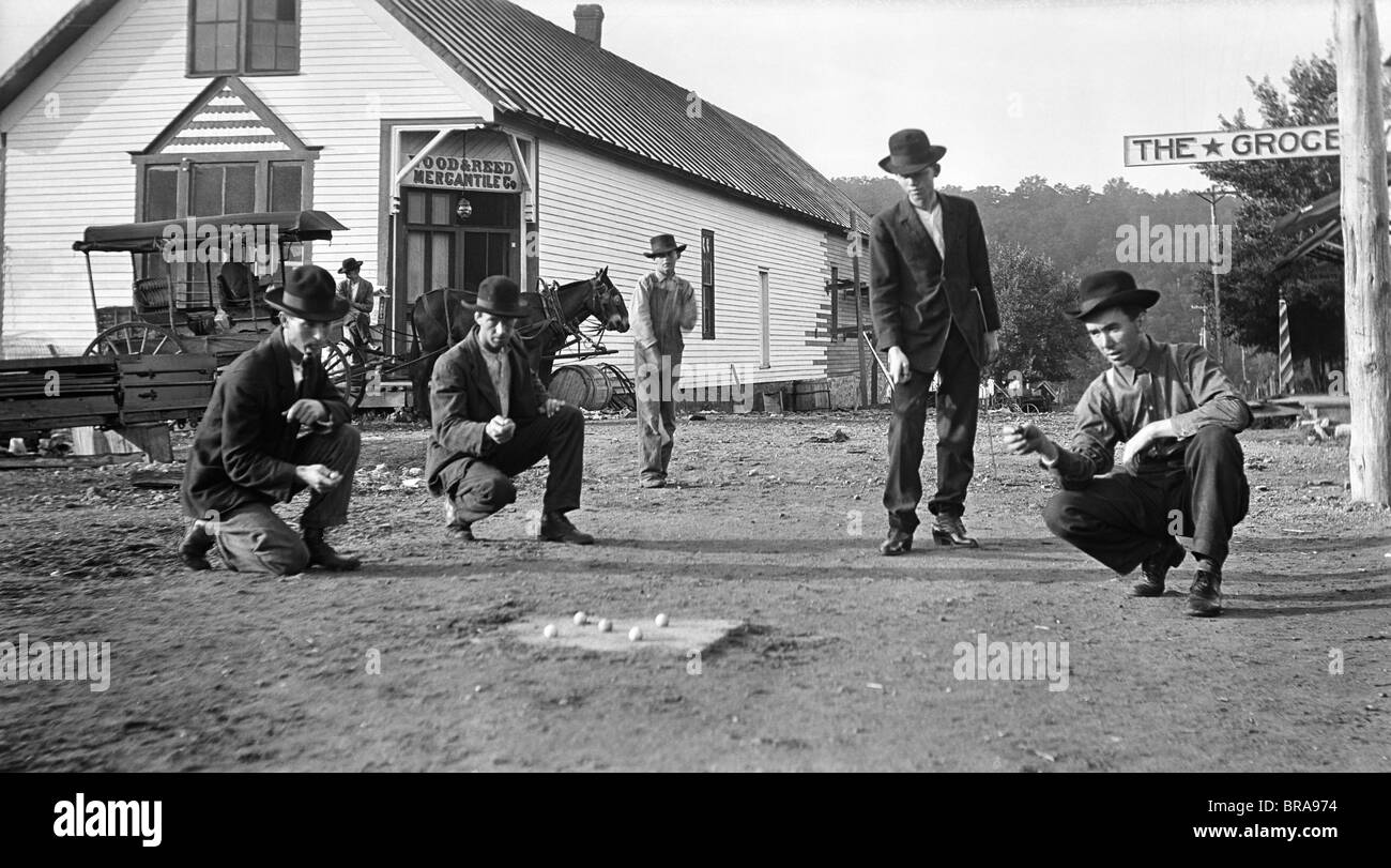 1910s MEN PLAYING MARBLES GAME OF HOSS IN ON STREETS OF GAINSVILLE MISSOURI IN THE OZARK HILL COUNTRY - Stock Image