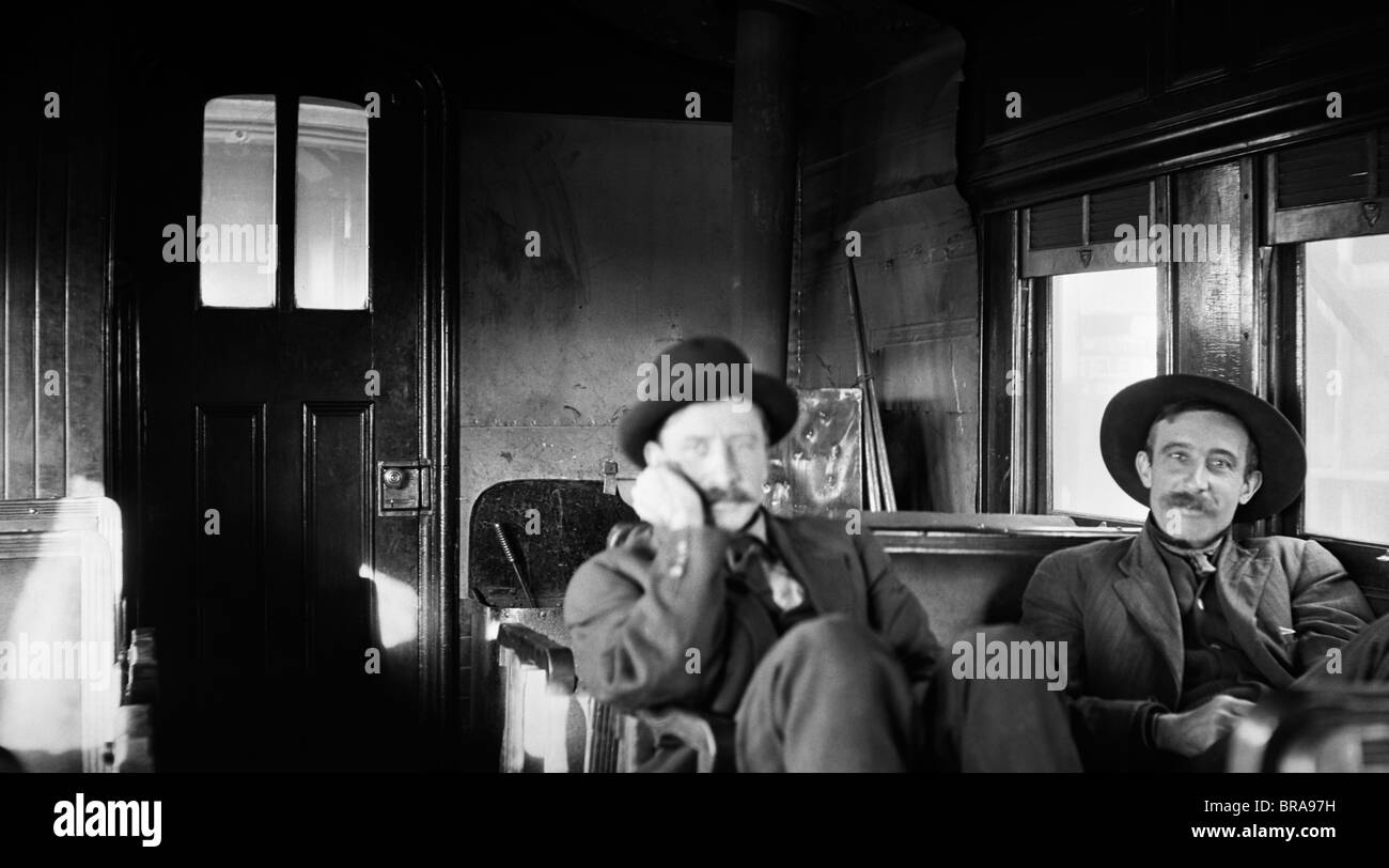 1900s TWO MEN PASSENGERS IN AN OLD ACCOMMODATION TRAIN CAR - Stock Image
