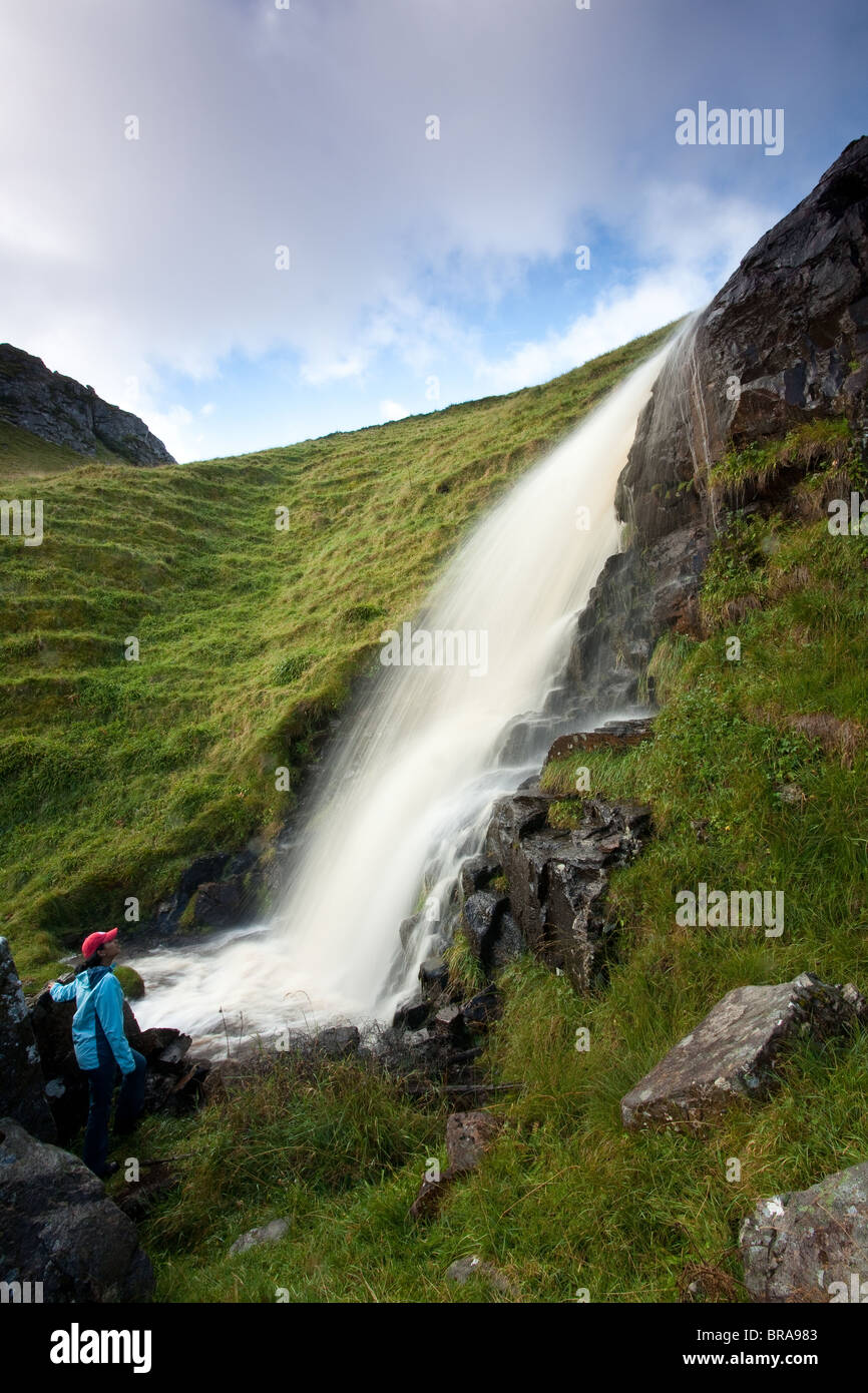 Girl looking at the beautiful waterfall at the island Runde, Atlantic west coast, Norway. - Stock Image