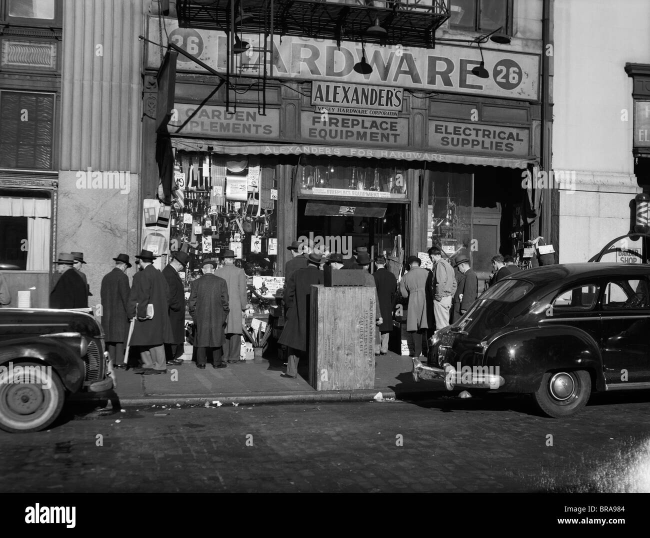 1940s NEW YORK CITY SIDEWALK CROWD GROUP PEOPLE MEN ONLY IN FRONT OF ALEXANDER'S HARDWARE STORE - Stock Image