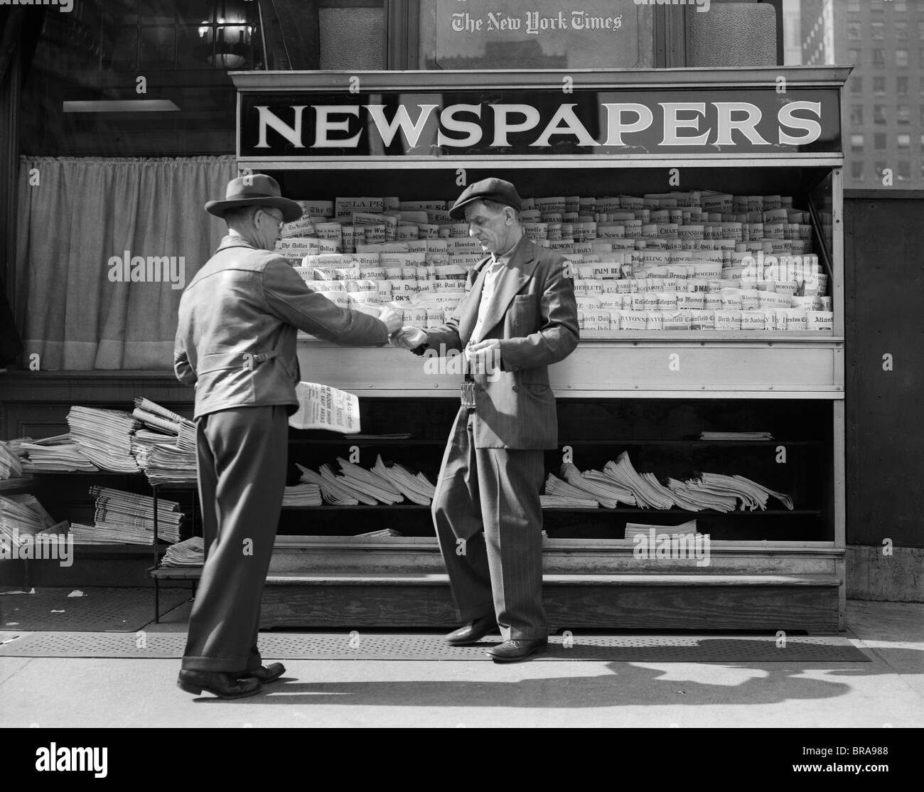1940s MAN BUYING NEWSPAPER FROM VENDOR ON SIDEWALK NEW YORK CITY
