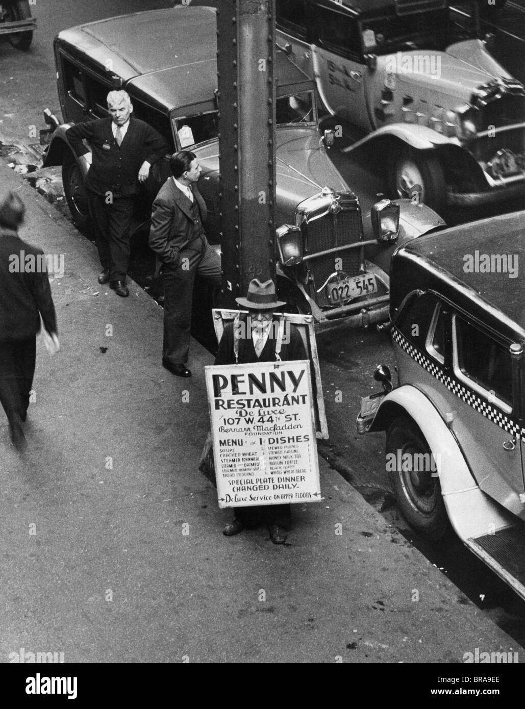 1930s NYC STREET DURING DEPRESSION WITH MAN WEARING SANDWICH BOARD ADVERTISING PENNY RESTAURANT - Stock Image
