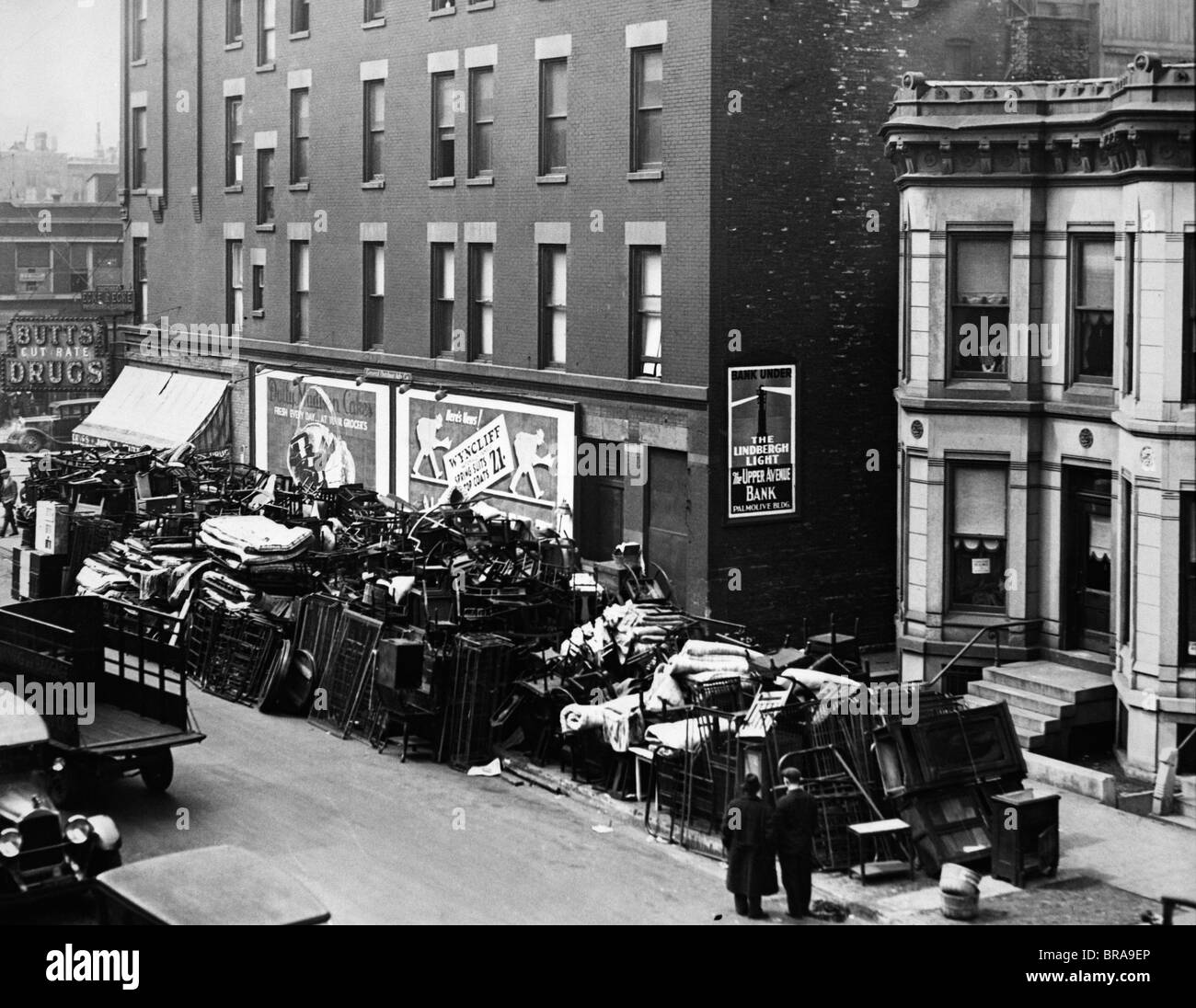 1930s GREAT DEPRESSION ERA MASS EVICTIONS PILES OF FURNITURE STACKED ALONG RESIDENTIAL STREET - Stock Image