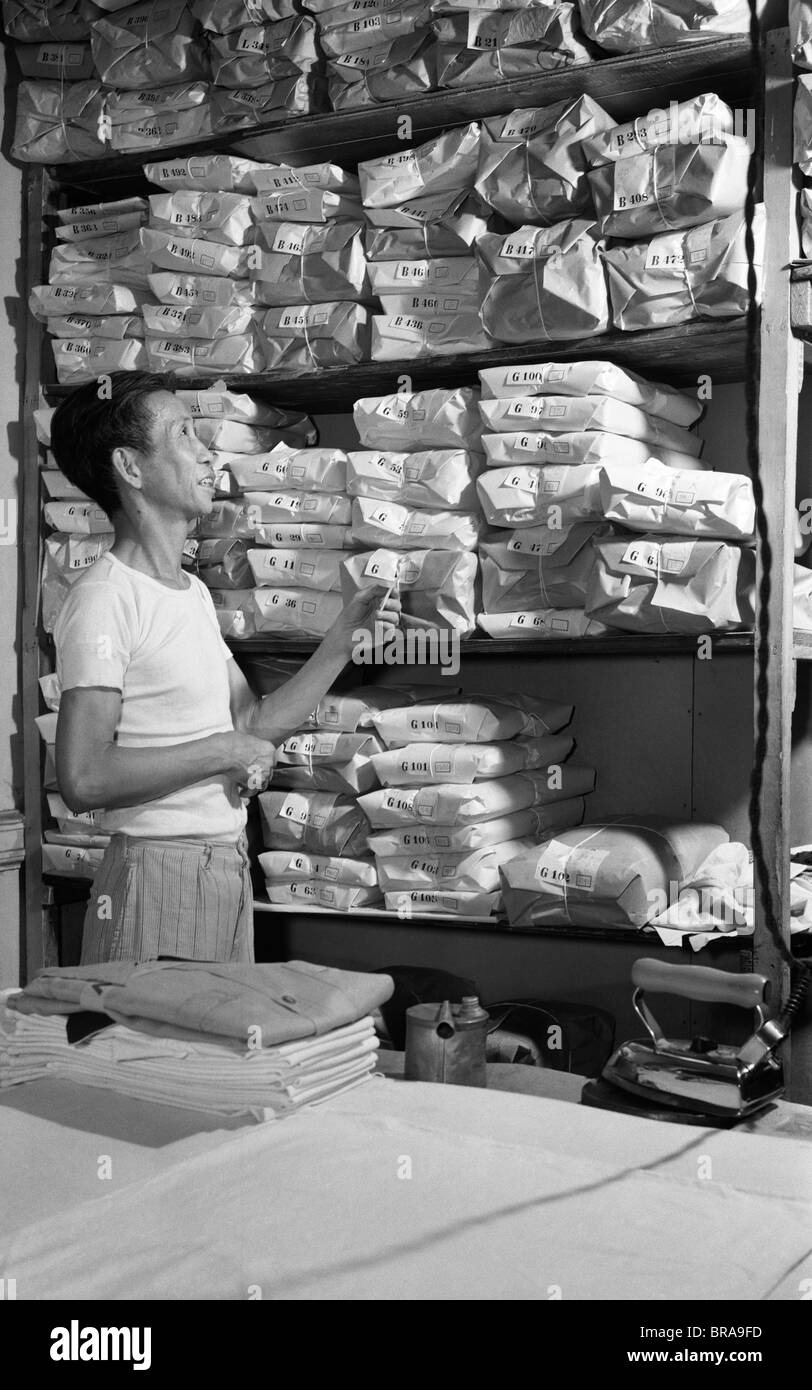 1940s ASIAN MAN HAND CHINESE LAUNDRY LOOKING AT SHELVES OF LAUNDRY WRAPPED IN BROWN PAPER - Stock Image
