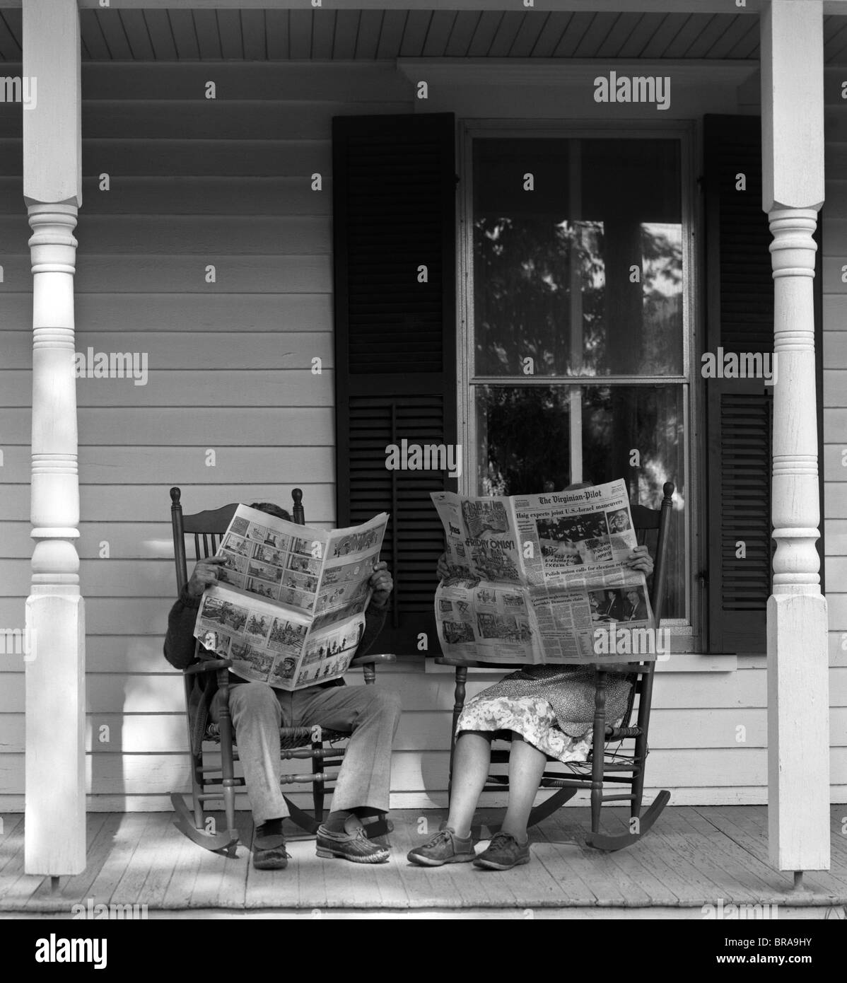 1950s 1960s COUPLE MAN WOMAN SITTING ON PORCH IN ROCKING CHAIRS HOLDING NEWSPAPERS UP HIDING THEIR FACES Stock Photo
