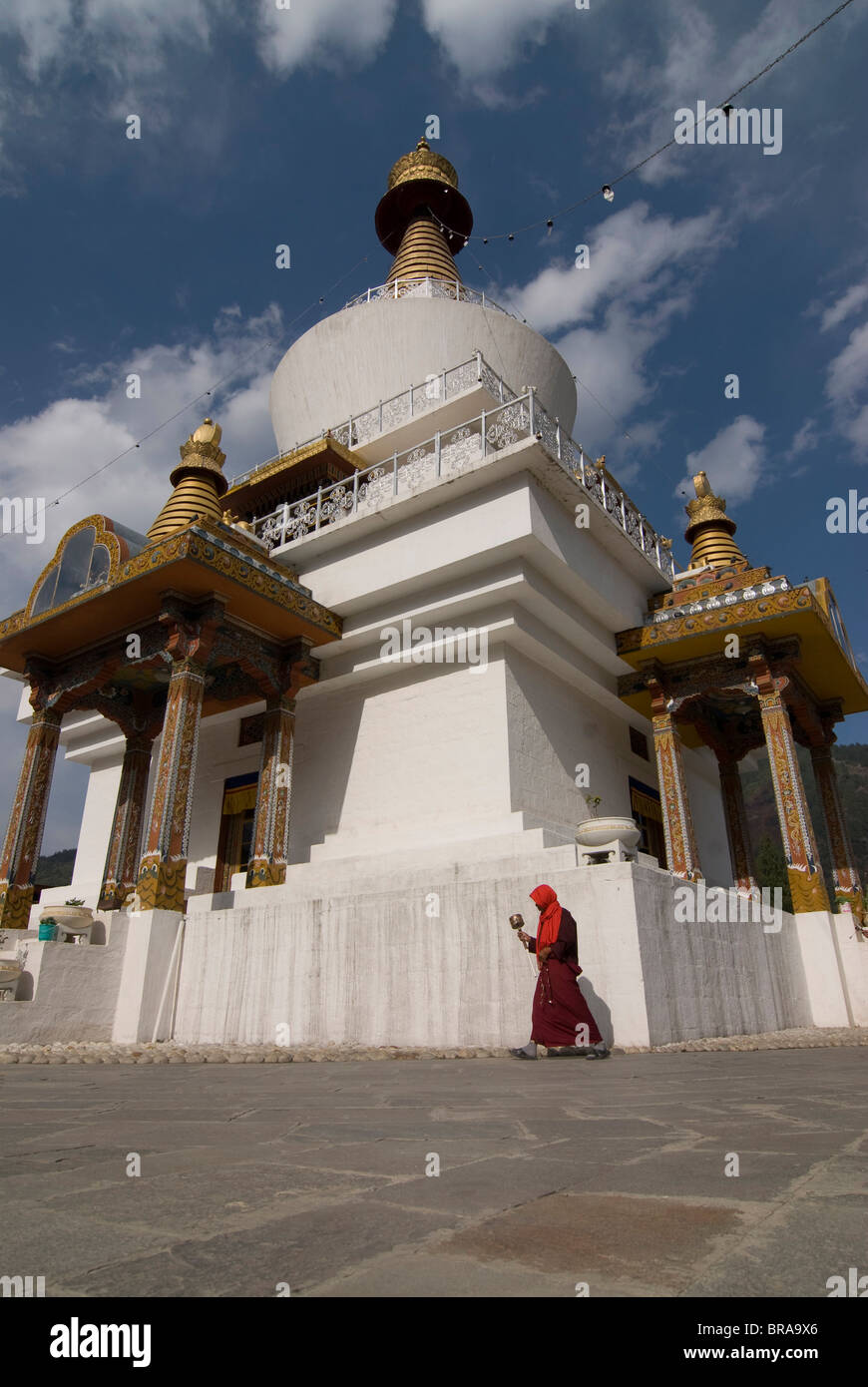 Pilgrim circling a white Stupa with prayer wheel in hand, Thimpu, Bhutan, Asia - Stock Image